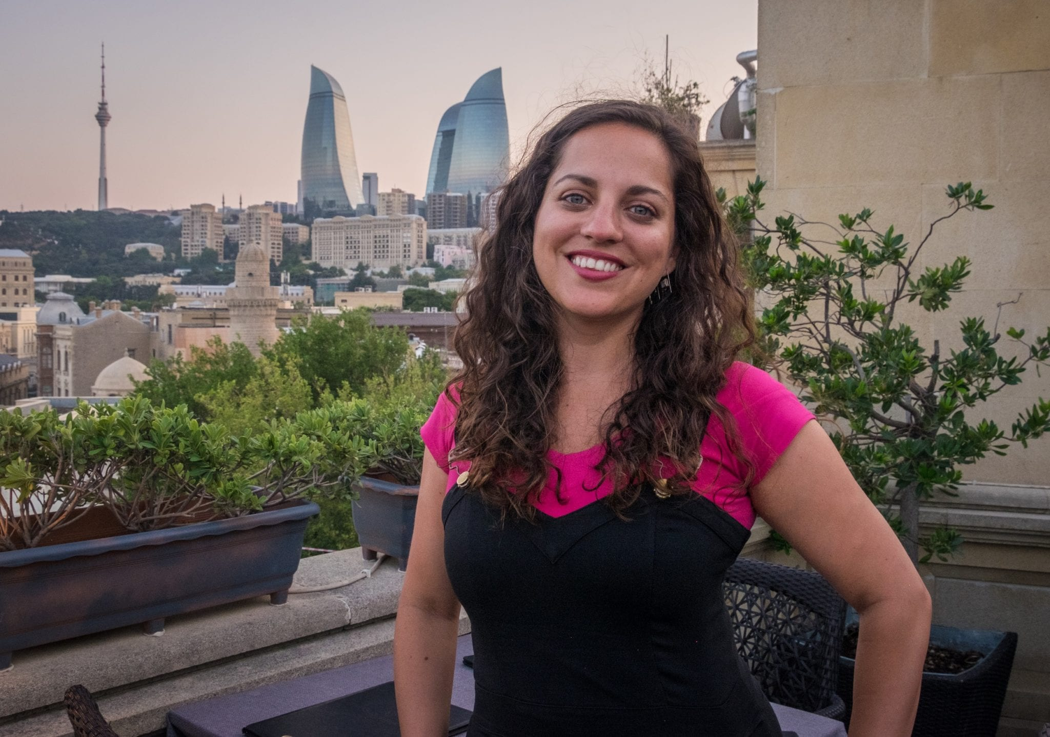 Kate poses on a balcony in front of the three flame-shaped towers of Azerbaijan as the sky turns pink at dusk.