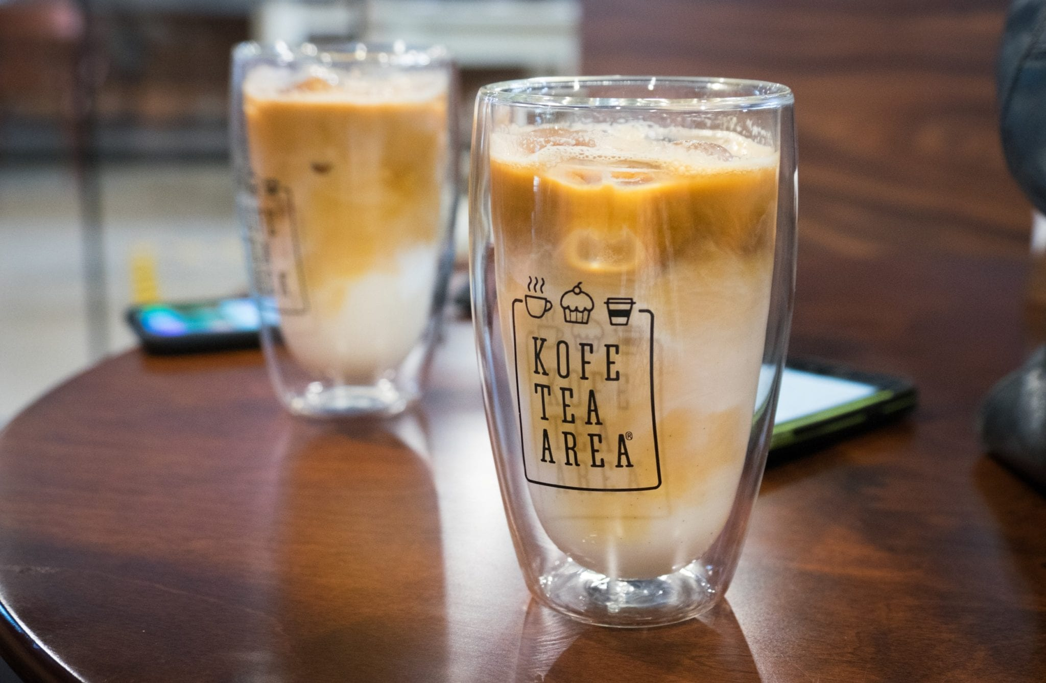 Two clear plastic large lattes with the milk and coffee swirling together, surrounded by ice.