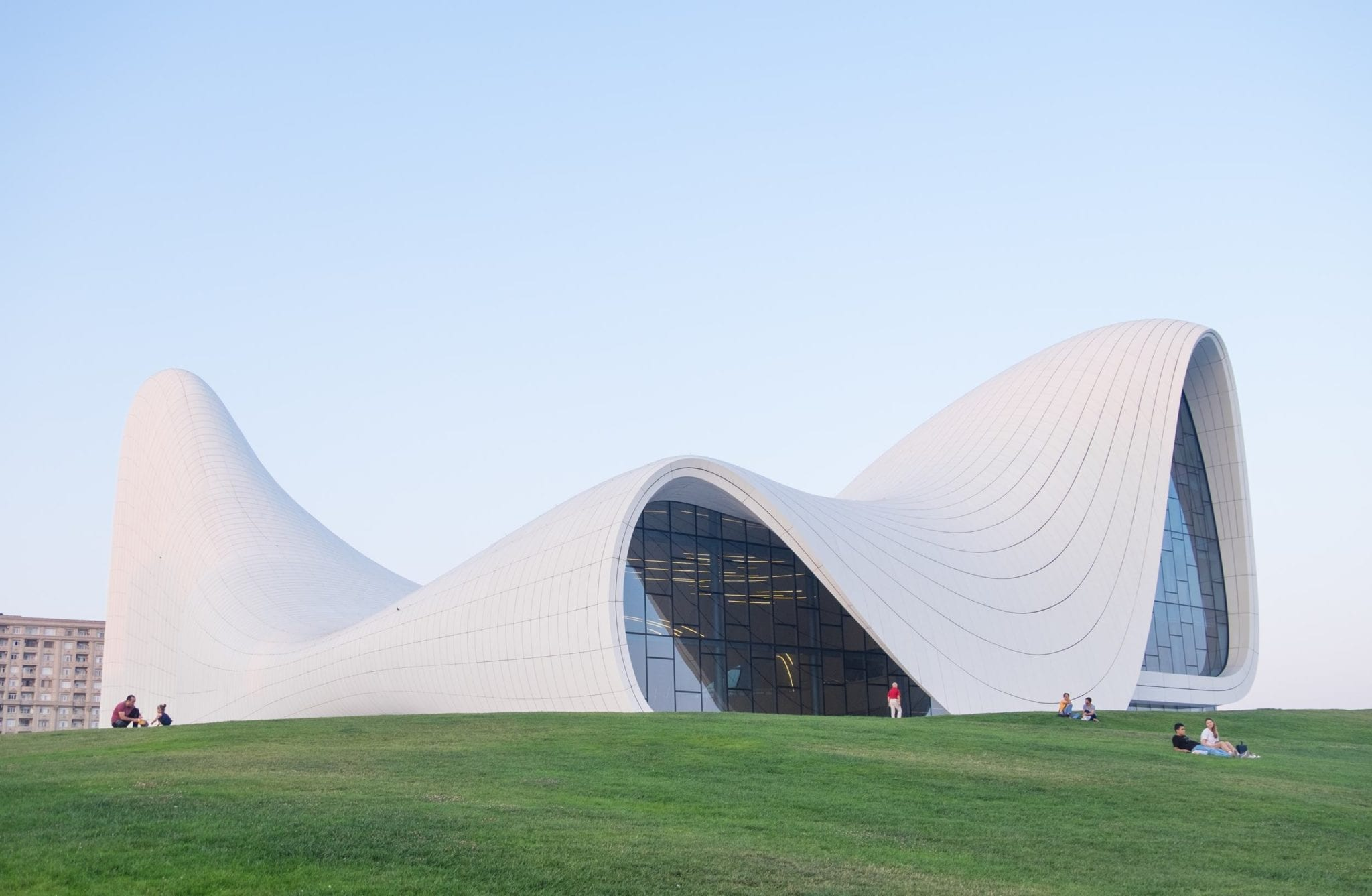 The swooping white curves of the modern Heydar Alivev Center, with people sitting on the grass in front of it.