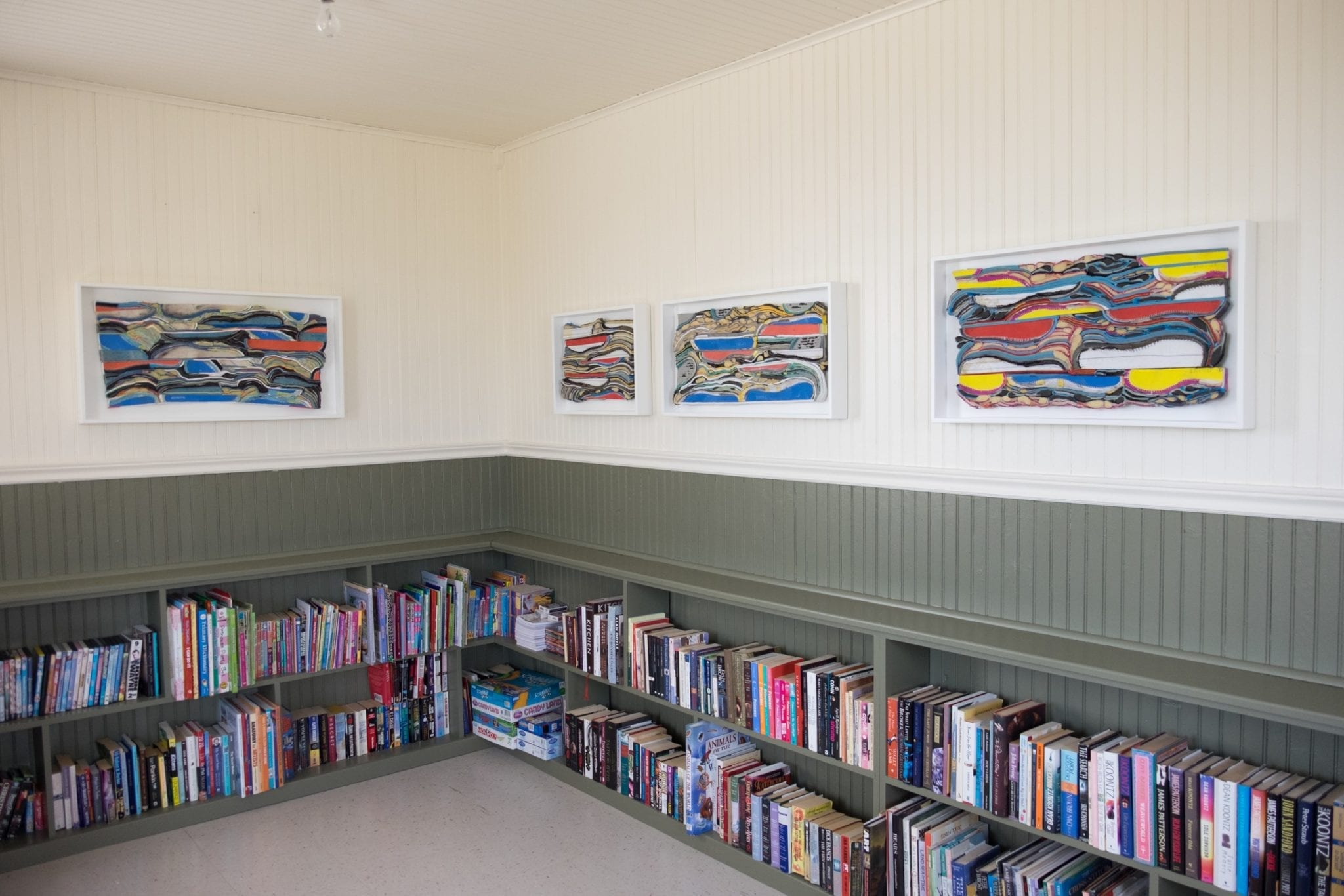 Above low bookshelves, four of Meghan Price's works of art, with the 3d layers of rubber from sneakers symbolizing layers of the Earth's crust.