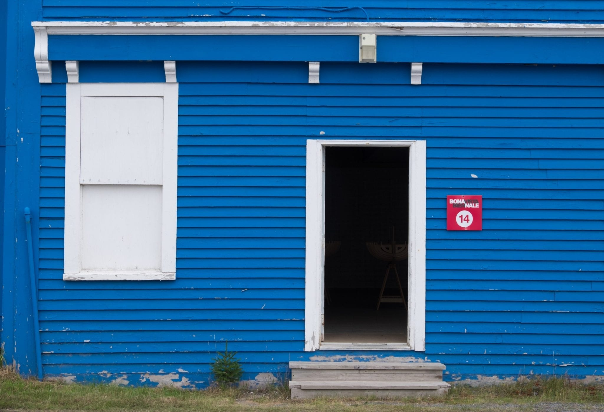 "A bright blue building with a red ""Bonavista Biennale"" sign to the right of the door."