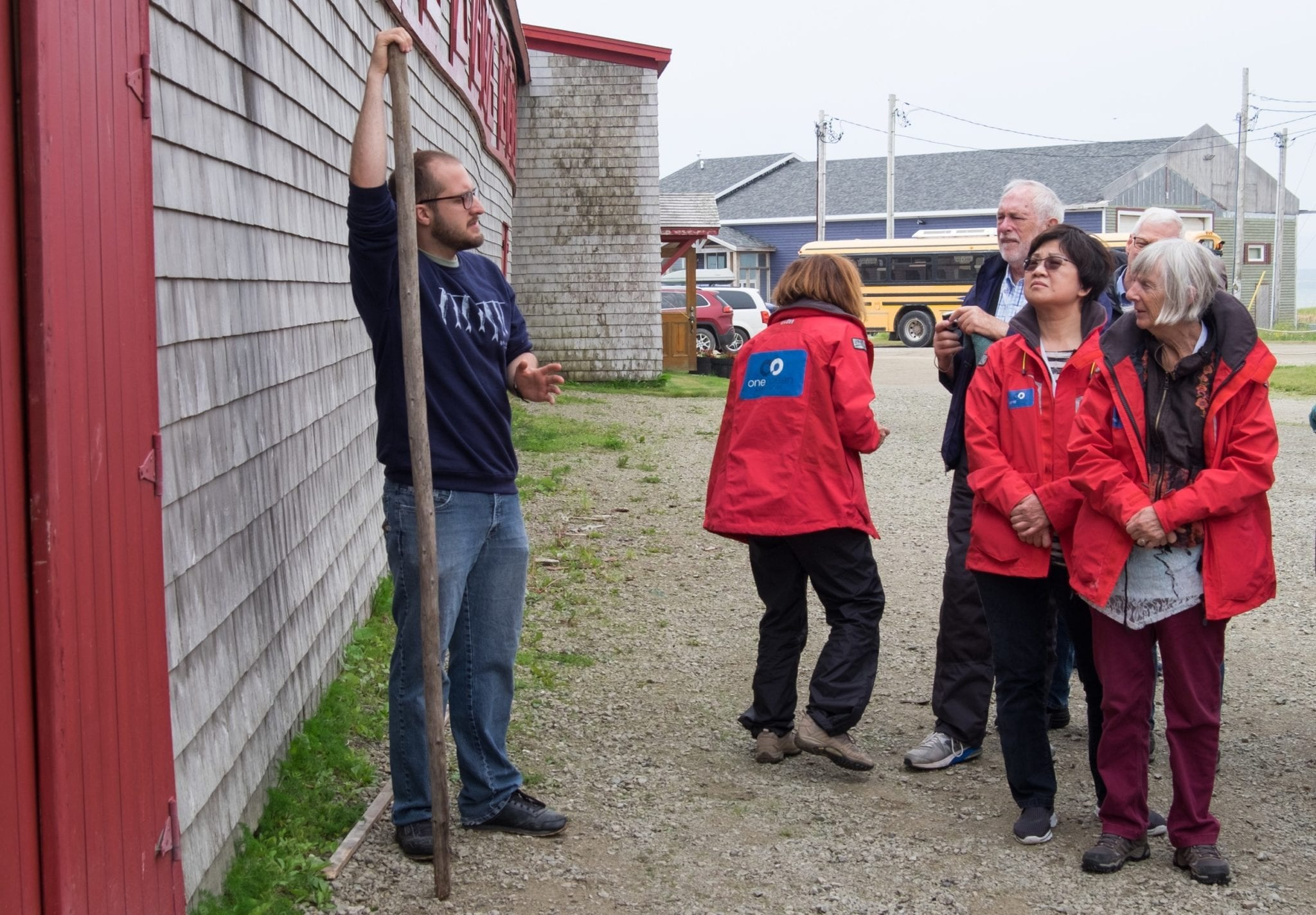 The smokehouse owner stands in front of the smokehouse holding a stick taller than him. Several older people wearing bright red OneOcean jackets listen to him talk.
