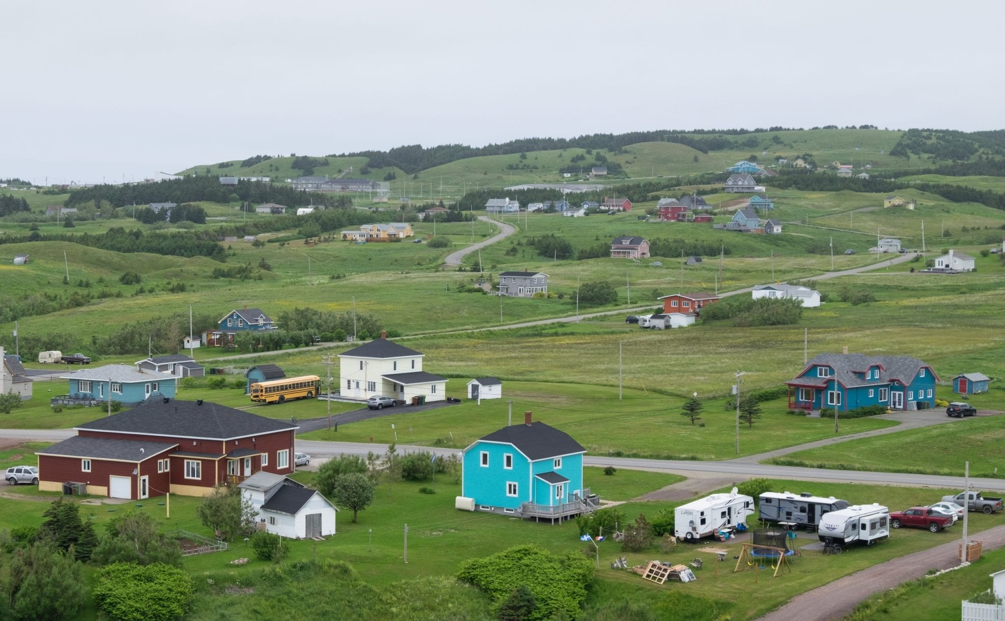 Tiny, brightly colored houses nestled into the hills of the Iles-de-la-Madeleine
