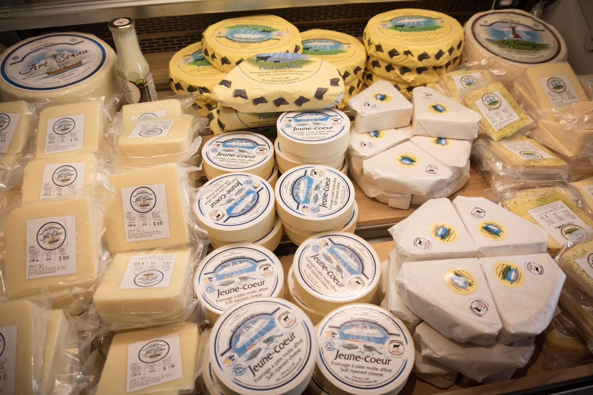 Piles of wrapped cheeses in a refrigerated container at Pied de Vent fromagerie in the Iles-de-la-Madeleine.