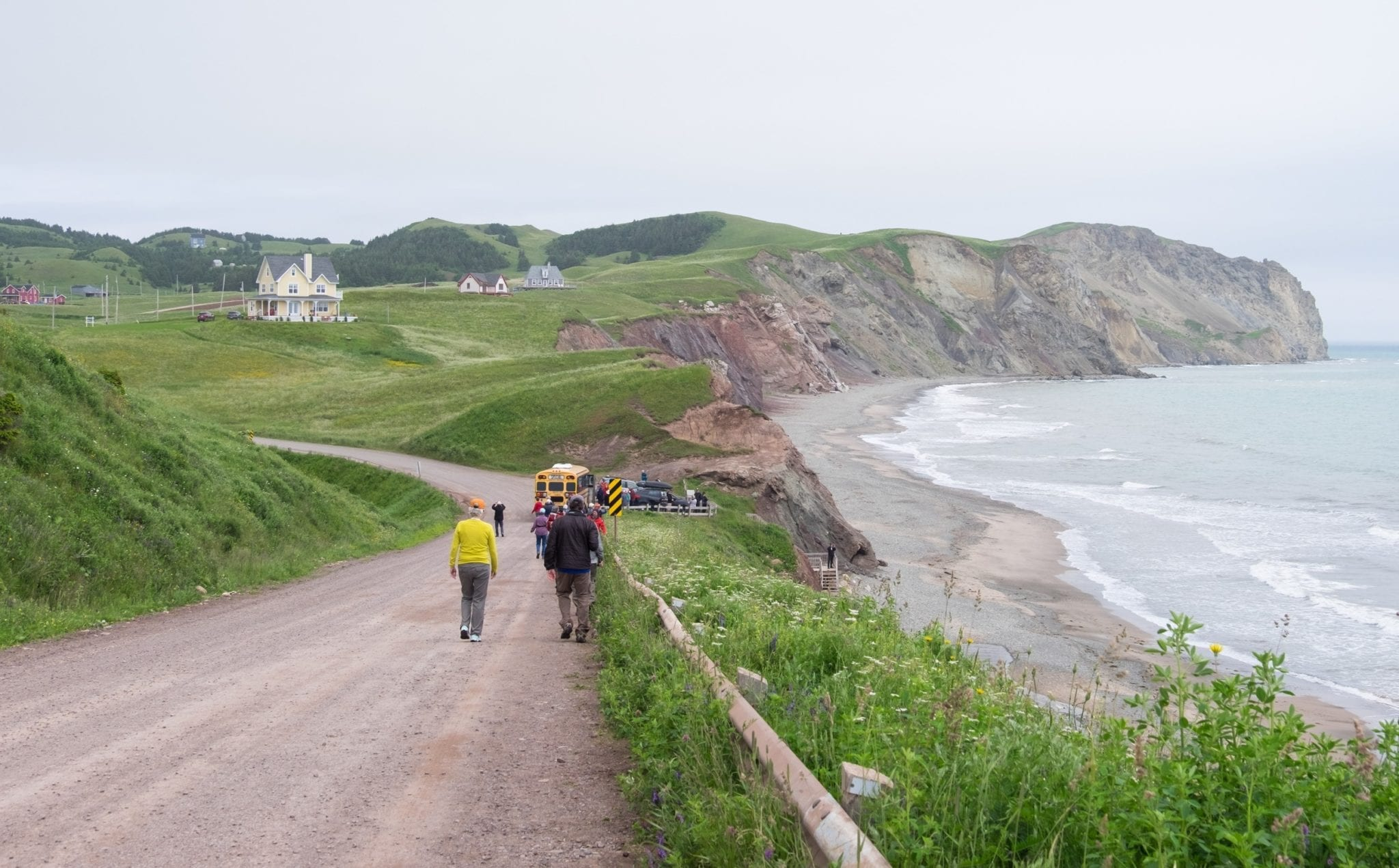 A group walks down a dirt road in the Iles-de-la-Madeleine; on the right is a gray cliff leading down to a rocky beach.