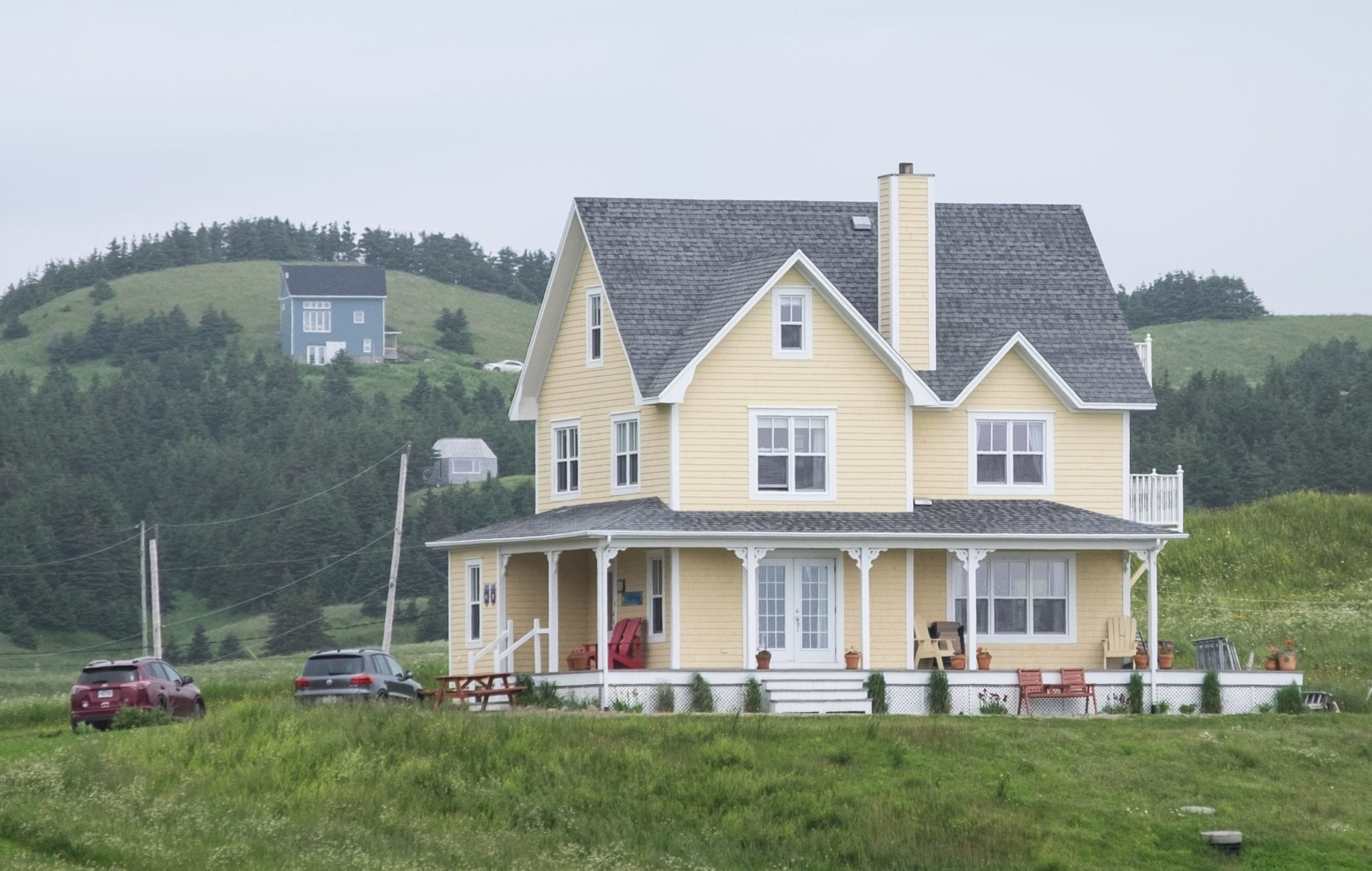 A large pale yellow house with a wraparound porch perched on a hill in the Iles-de-la-Madeleine.