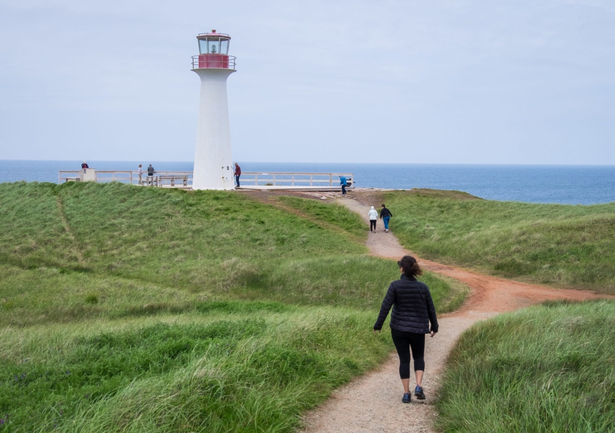Kate walks along the path on a grassy hill to a white lighthouse in the Iles-de-la-Madeleine.