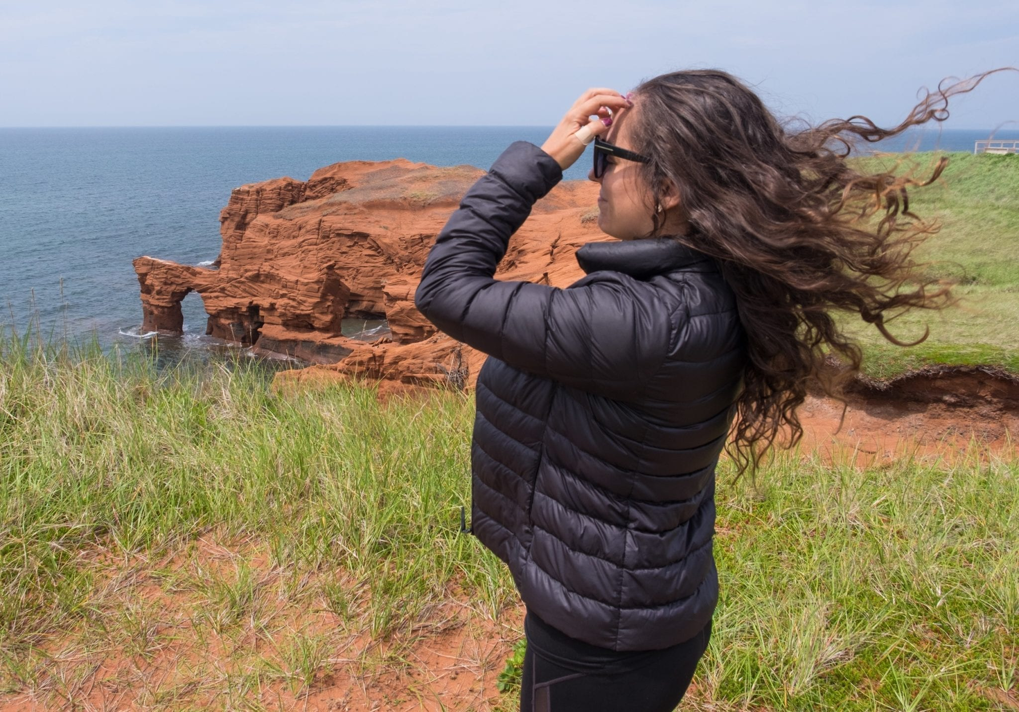 Kate stands in front of red cliffs and stands sideways to the camera, and you can see the wind is blowing her long curly hair straight upwards!