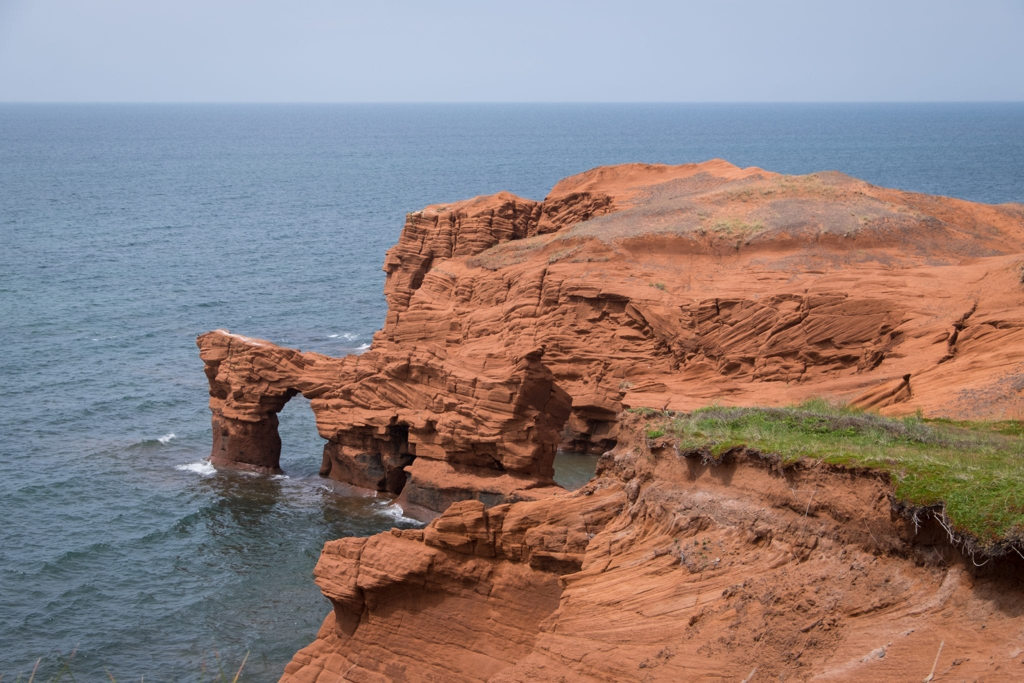 Bright red cliffs plunge into the sea on the Îles-de-la-Madeleine, Quebec.