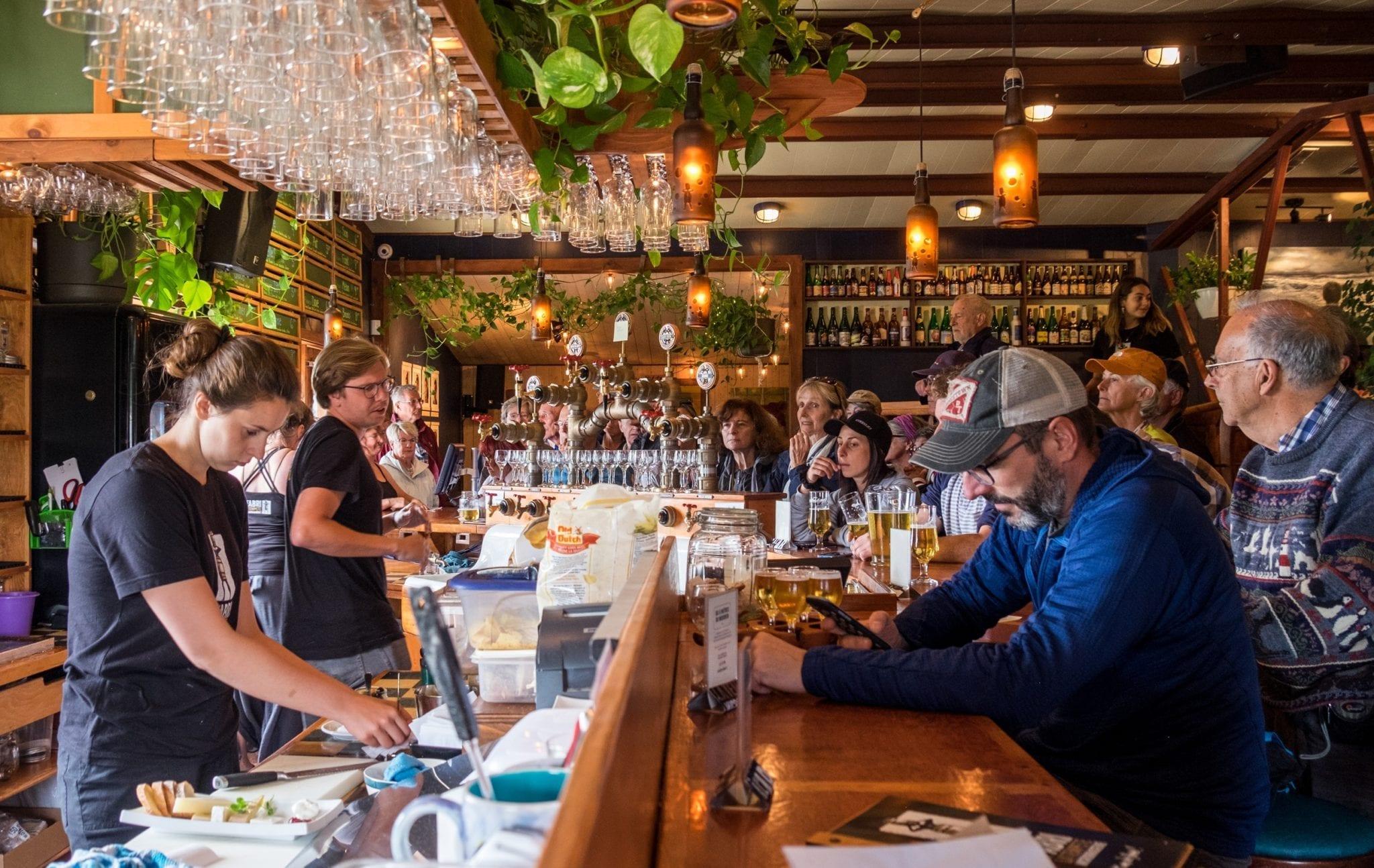 Bartenders serve beer to patrons at L'abri de la Tempete brewery in the Iles-de-la-Madeleine.