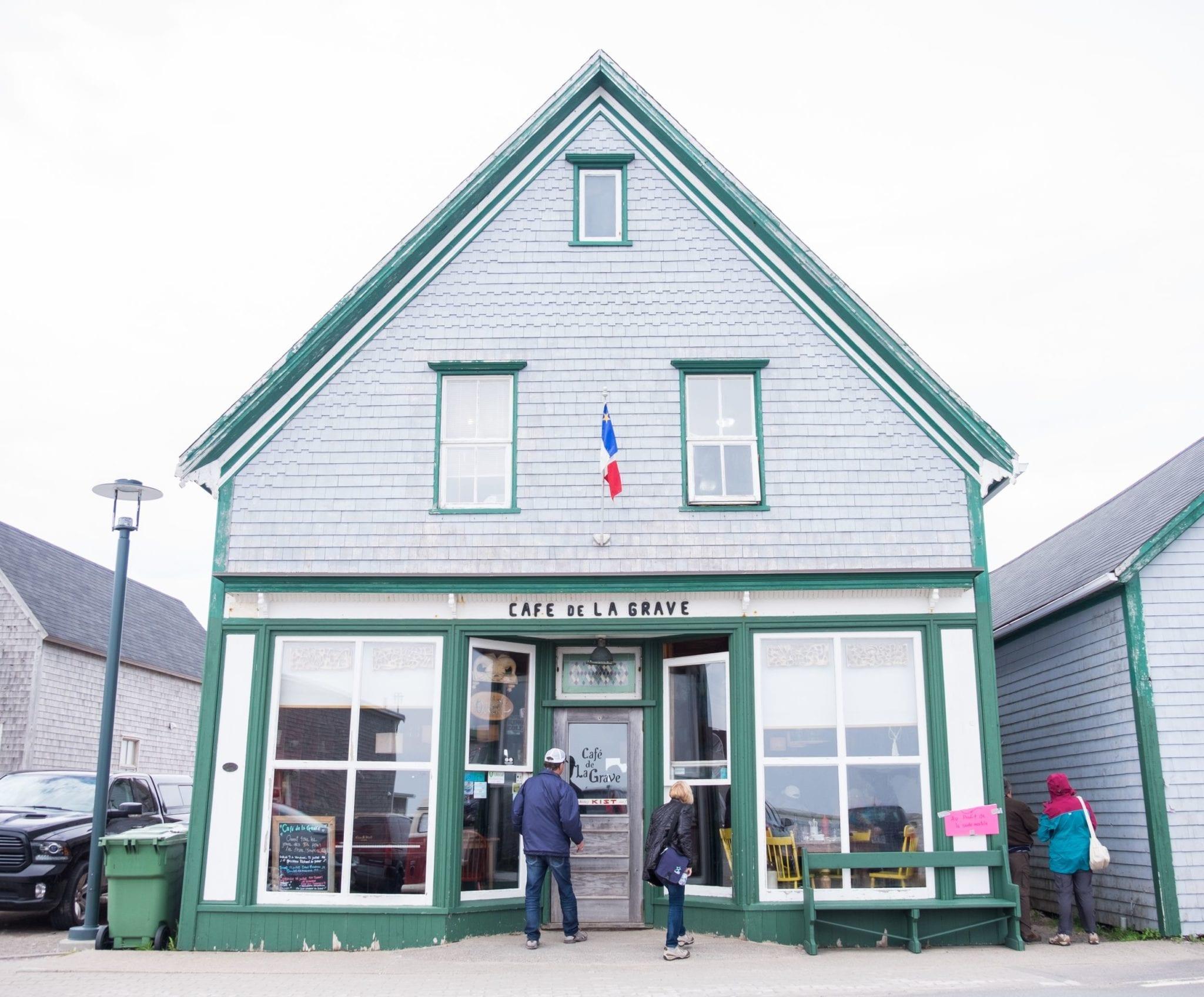 "A gray house with green trim reading ""Cafe de La Grave."""