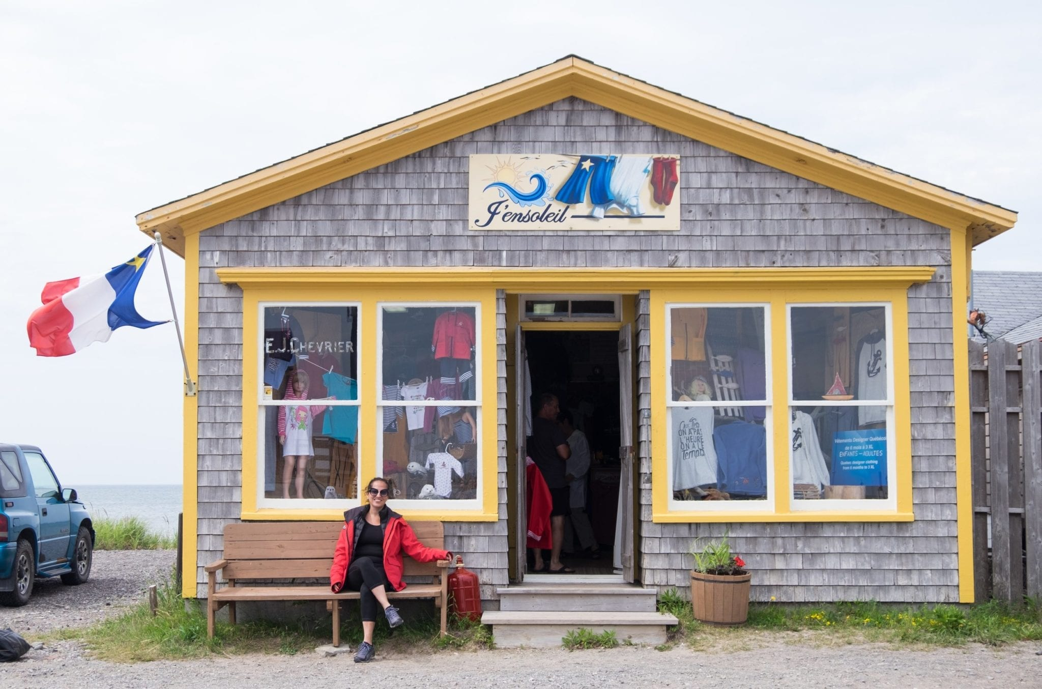 Kate sits on a bench in front of a gray shop with yellow trim and a red white and blue Acadian flag with a yellow star on it.