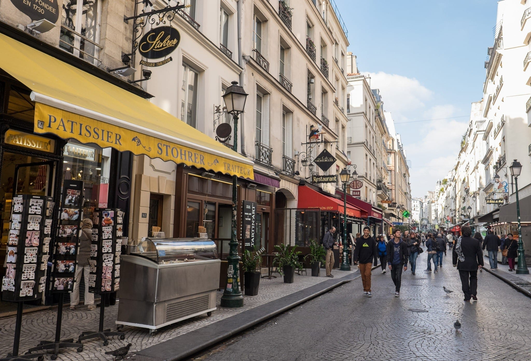 Best Places to Stay in Paris: a photo of Rue Montorgueil, lined with food shops and people walking down the street. In front is a shop with a bright yellow awning.