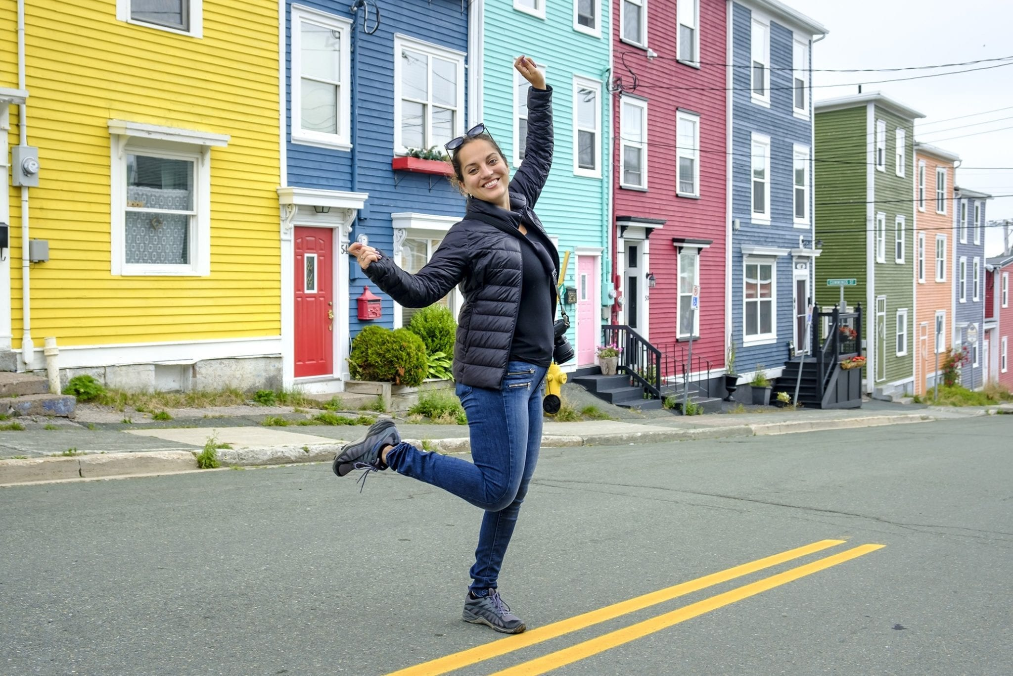 Kate dances in the street in front of a row of brightly painted houses in St. John's.