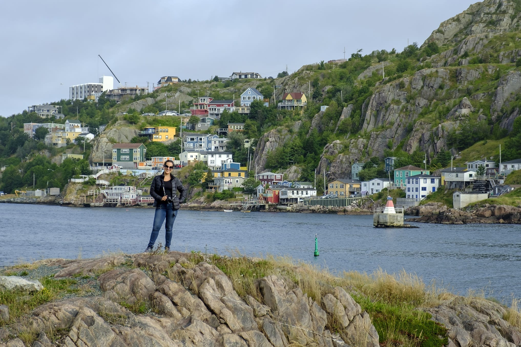 Kate stands on a cliff in Newfoundland in front of the bay and the colorful homes of St. John's behind her.