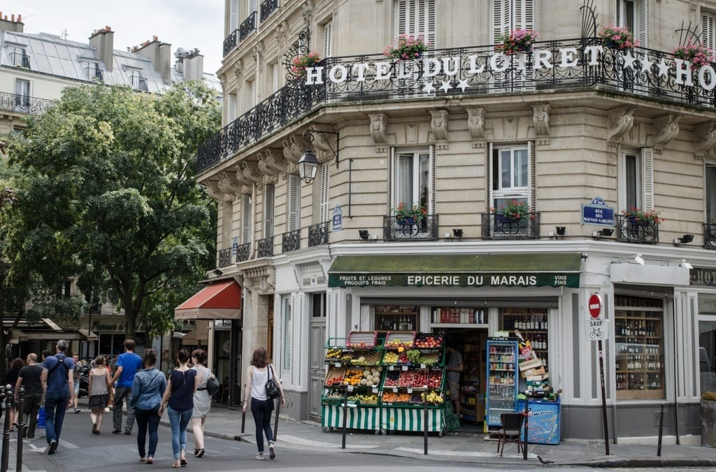 Where to Stay in Paris: a hotel in The Marais, a fruit shop at the base, with people walking by.