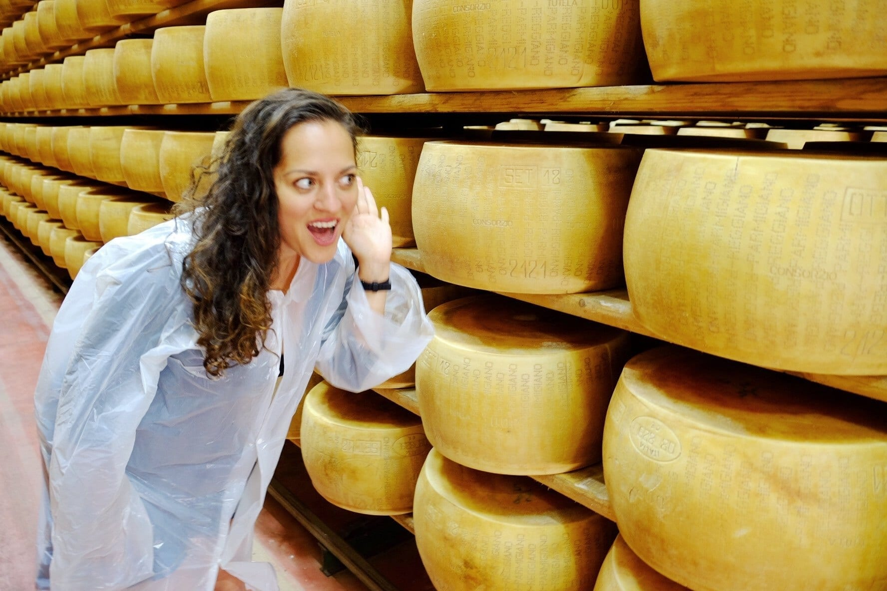 Kate stands in front of shelves of parmigiana reggiano wheels. She wears a protective robe and leans in with her hand to her ear, as if listening to the cheese.