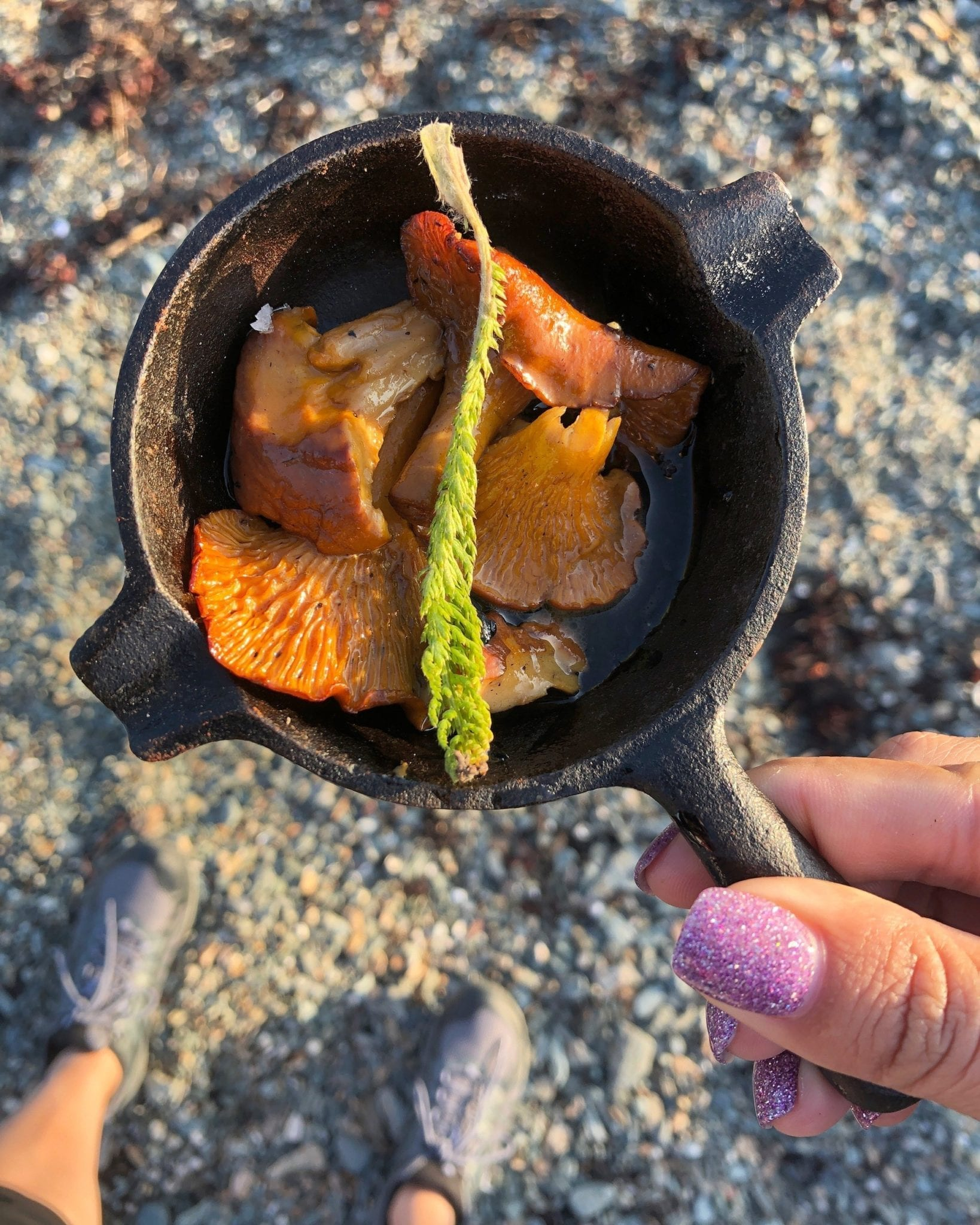 Kate holds a tiny cast iron skillet filled with chanterelle mushrooms and a spring of fresh green herbs. Beneath her you can see the sand and her purple hiking shoes,