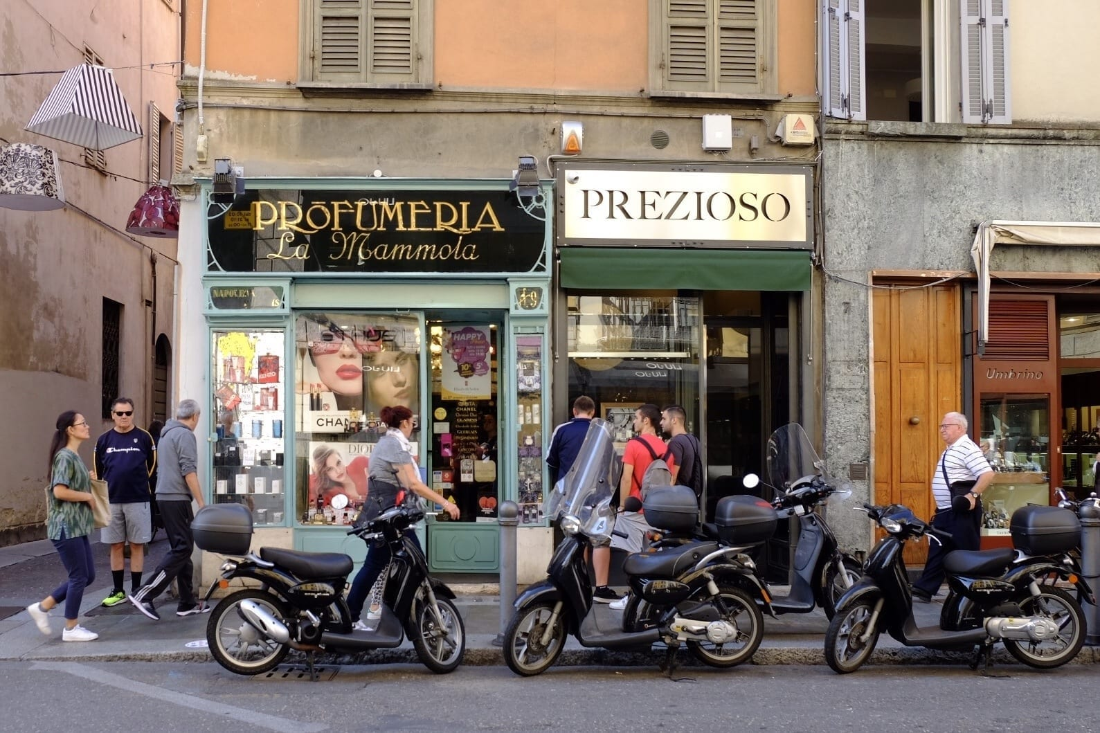 A street scene with old-fashioned stores with moss-green paint in Parma, Italy. Three motorbikes are parked in front of the stores and pedestrians are walking behind them.