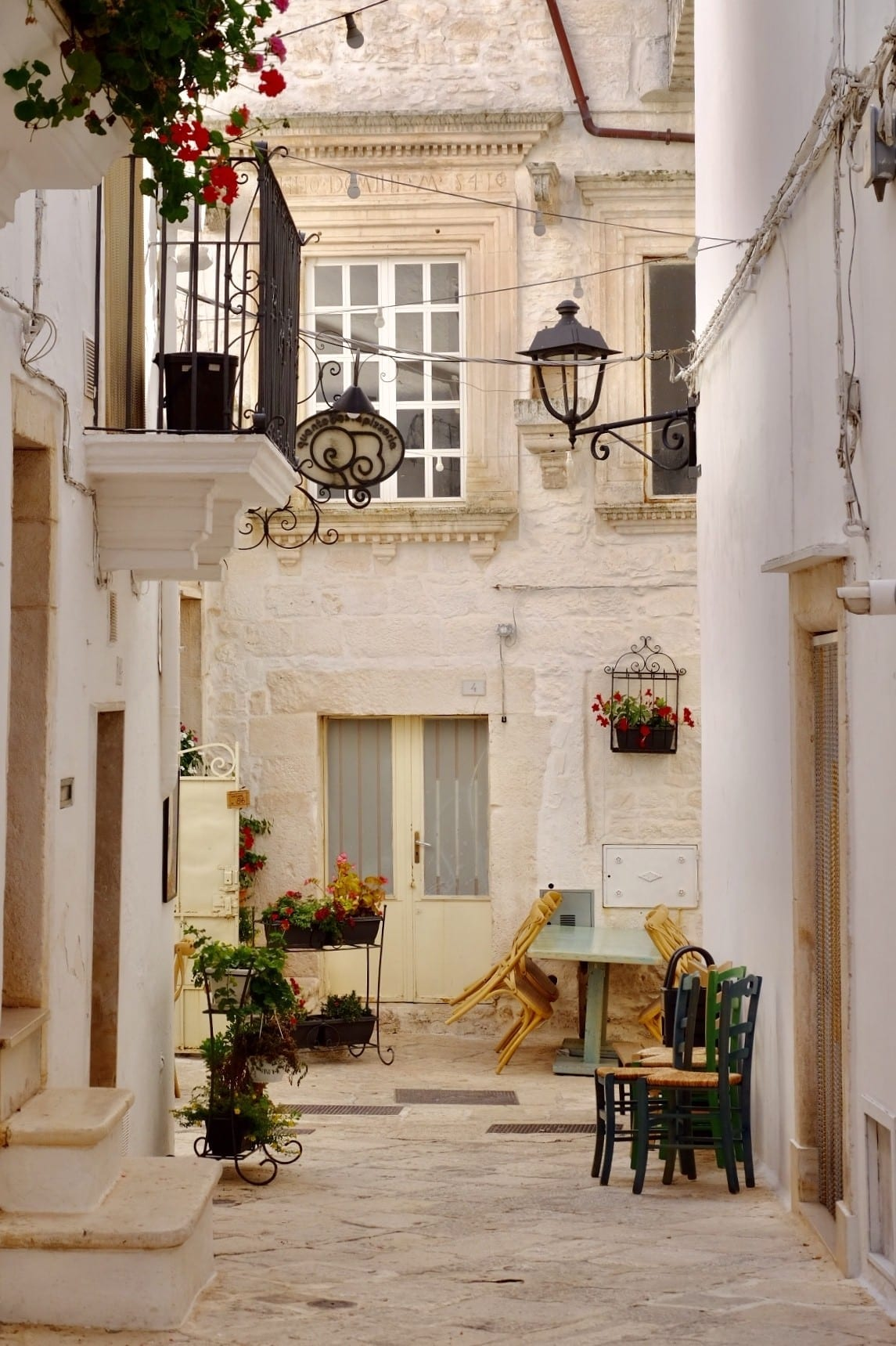 A street in the white city of Locorotondo in Puglia: all white and green. White city walls, green chairs next to a wall, green plants everywhere, black iron streetlamp. A perfect Italian town.