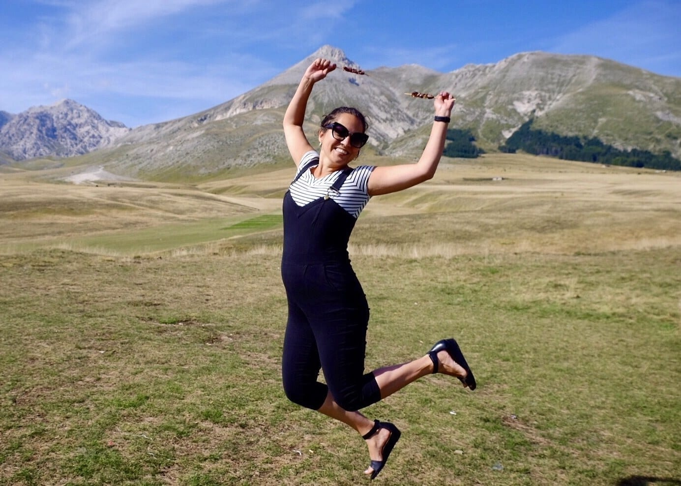 Kate wears overalls and jumps in the air, holding skewers of lamb in each hand, mountains and blue sky behind her, in Gran Sasso National Park.
