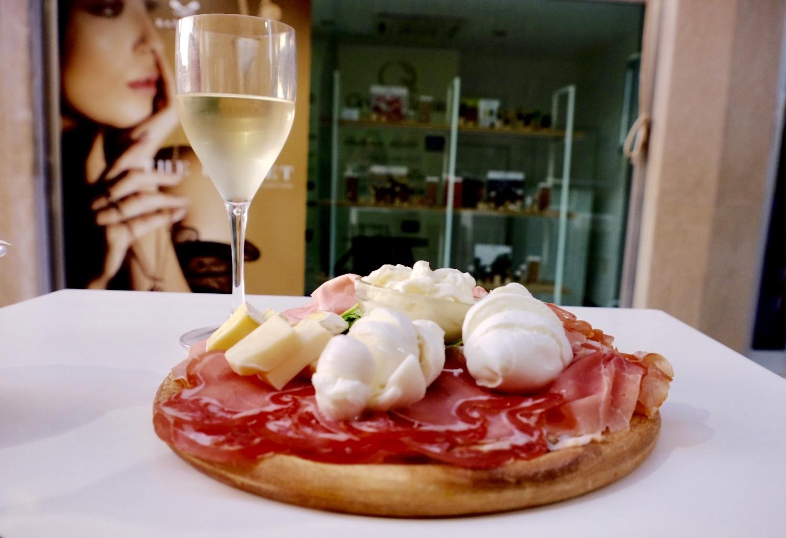 A glass of sparkling white wine next to a tangliere (plate of meat and cheese) in Lecce, Italy: topped with several kinds of ham, burrata mozzarella, and other hams and cheeses.