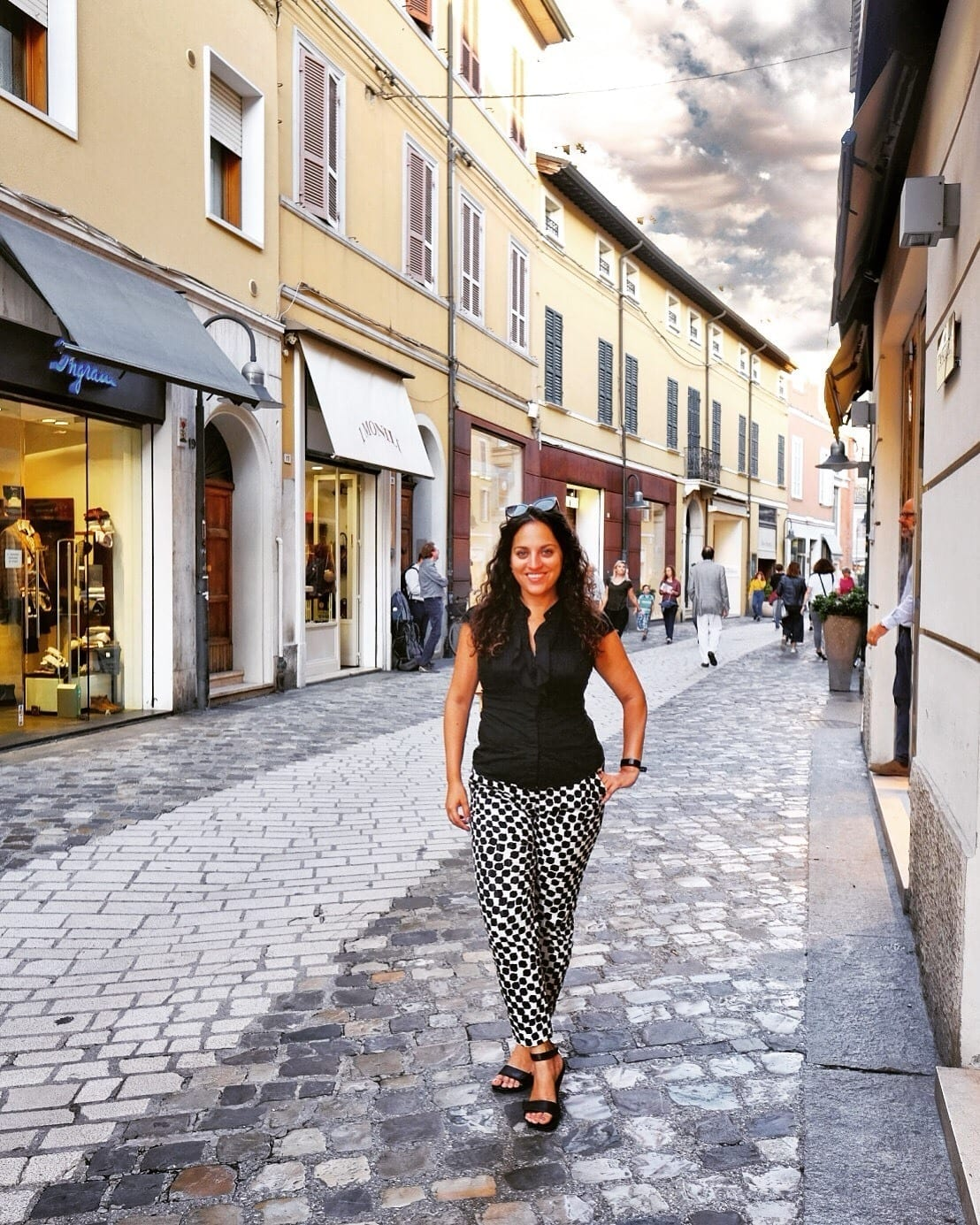 Kate stands on a cobblestone street in Ravenna, Italy, in front of boutique shops in yellow buildings. She wears black and white patterned pants and a sleeveless black blouse.
