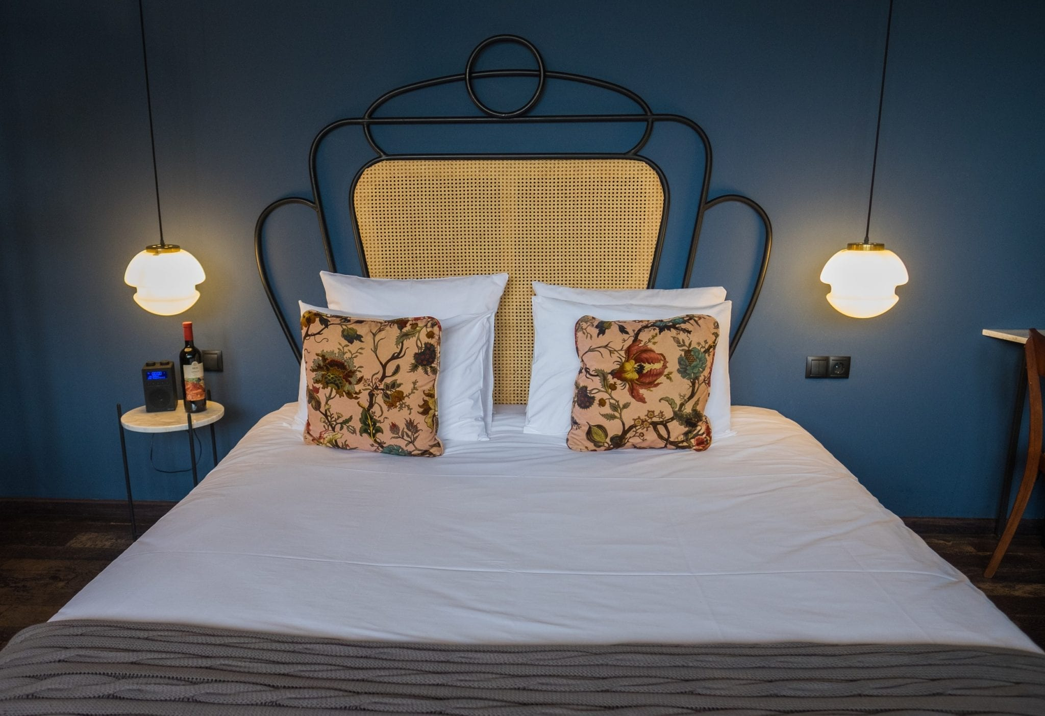 A bed with white sheets, yellow pillows, and a yellow and iron headboard set against a dark blue-green wall with hangings lamps and small modern marble-topped side tables.