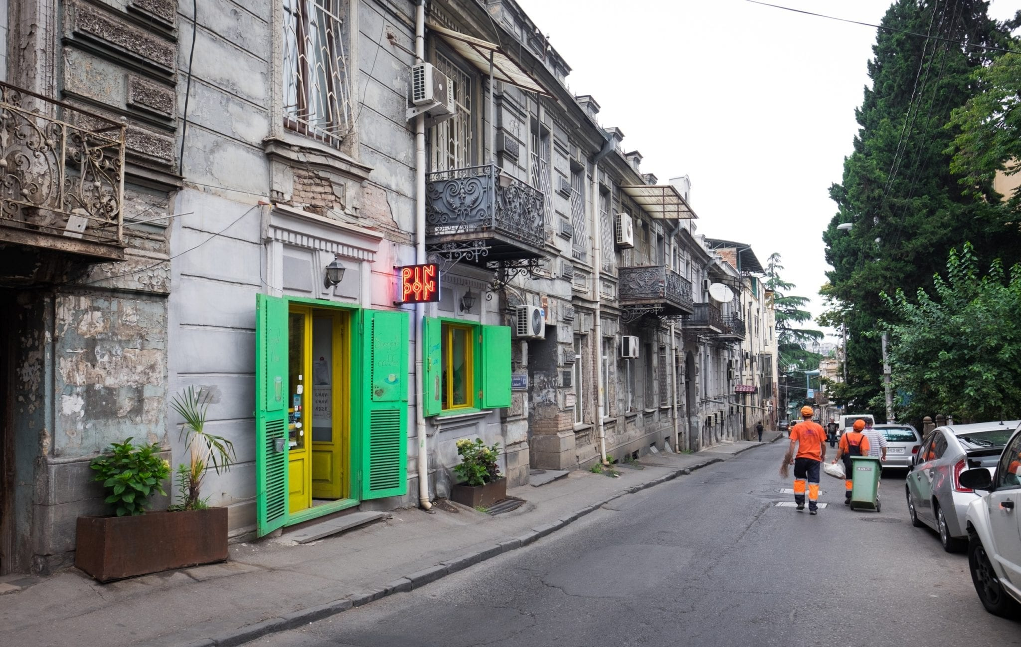 A gray street in Tbilisi interrupted by a bright neon green and yellow coffeeshop.
