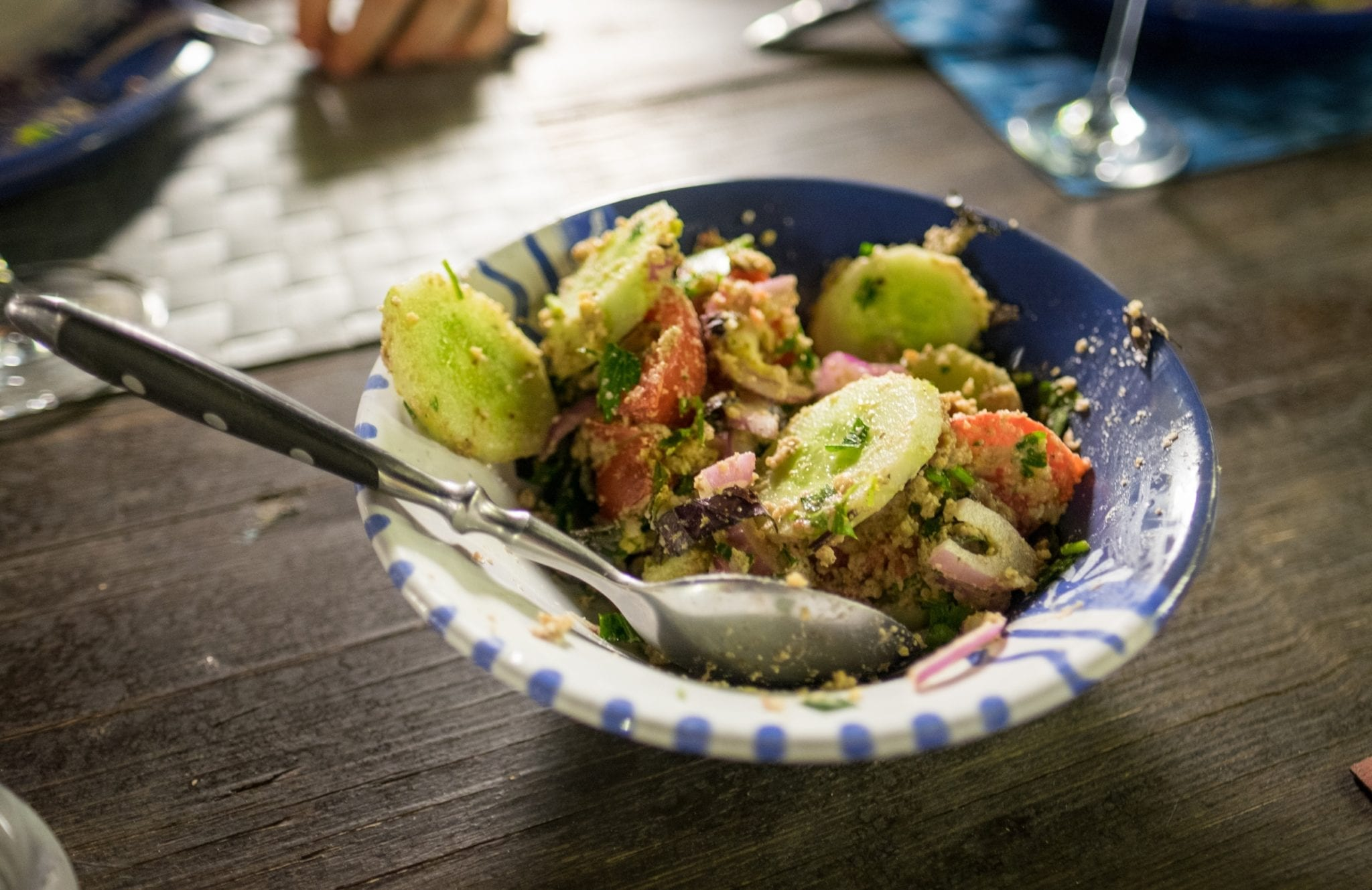 A bowl filled with cucumbers, tomatoes and red onions with walnut and herb paste.