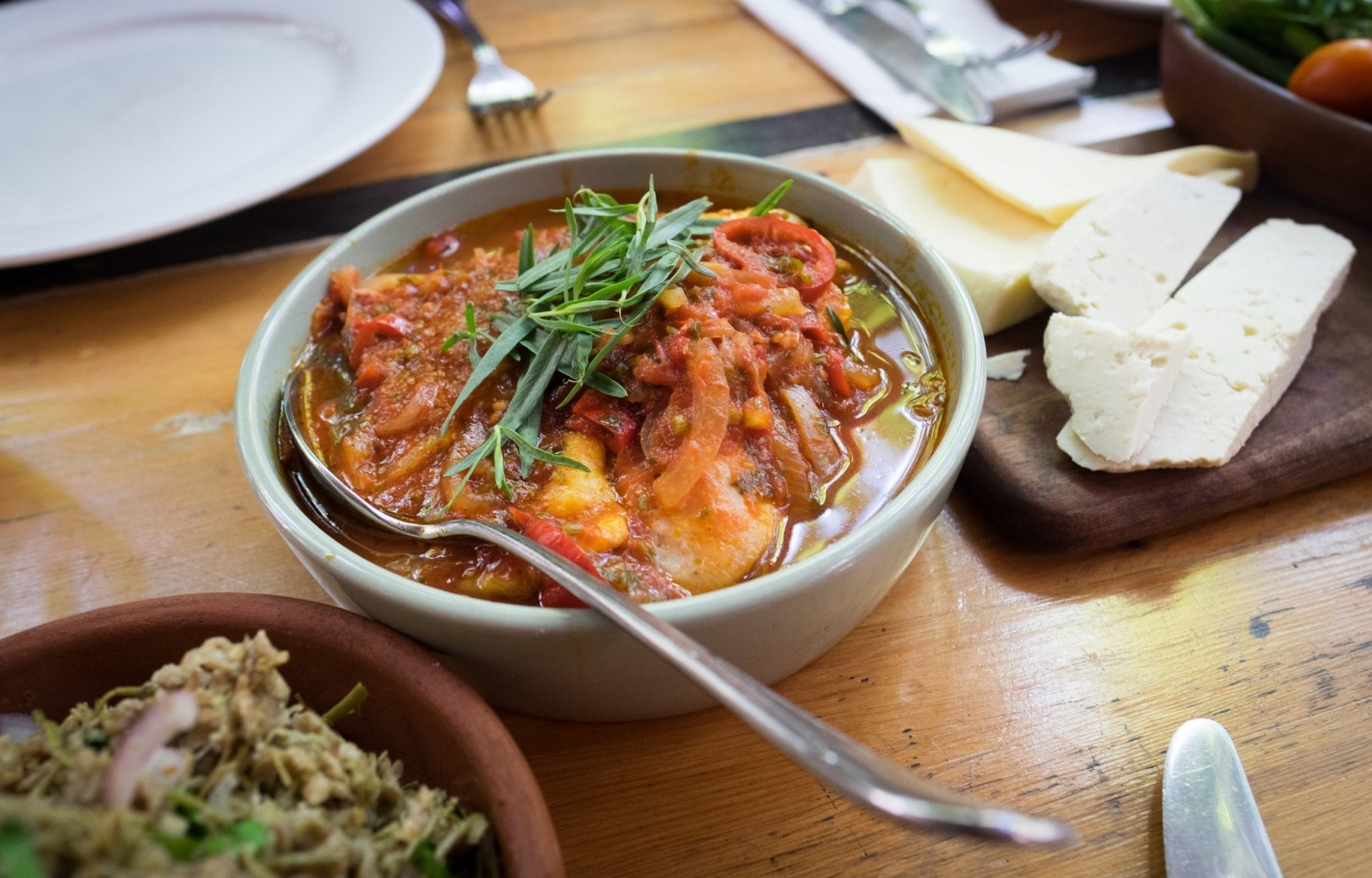 A bowl filled with chicken, tomatoes and onions and topped with a spring of rosemary.