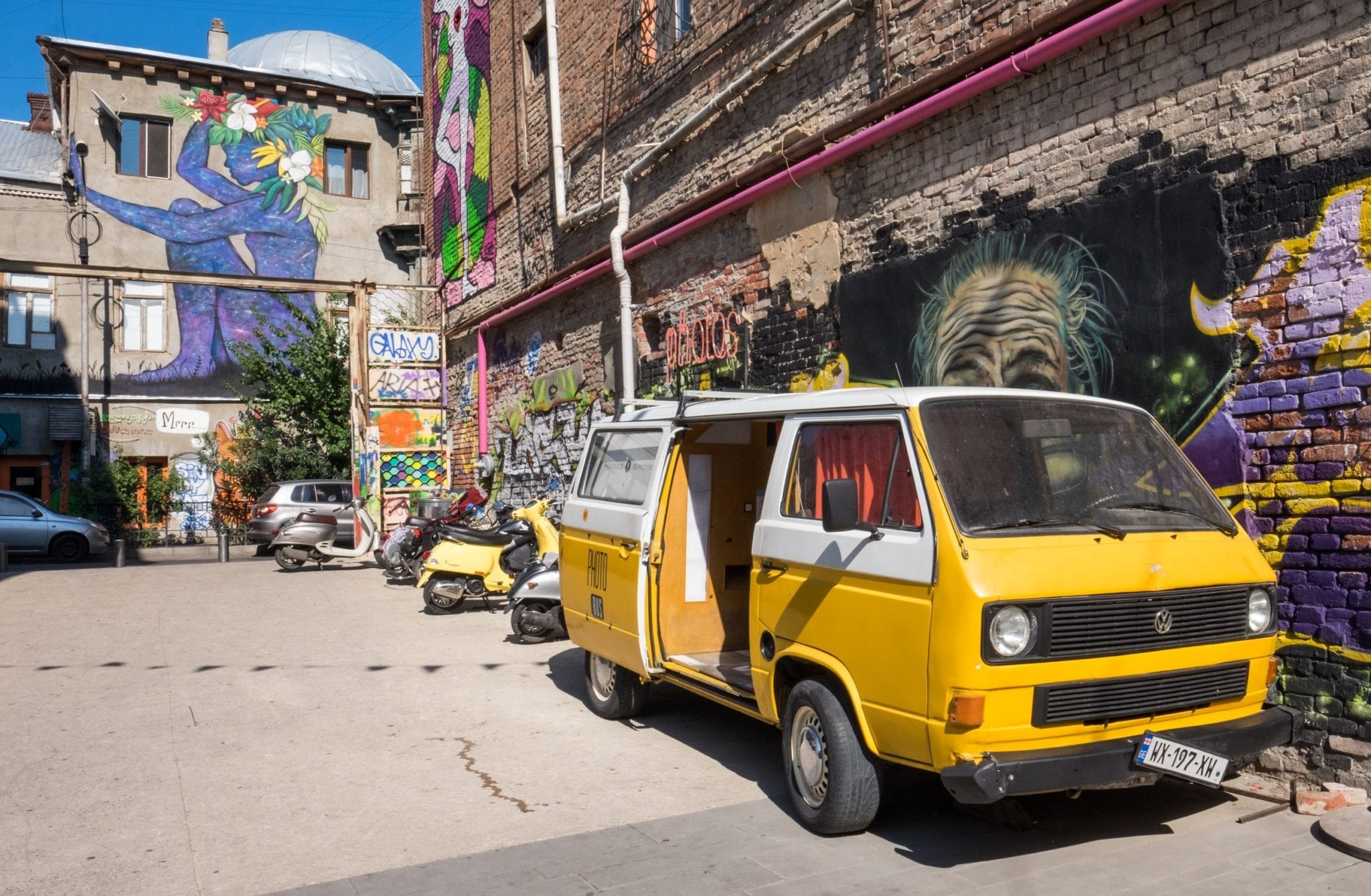 A yellow van parked against a street art-covered wall, with more murals in the background. On the street in Tbilisi.