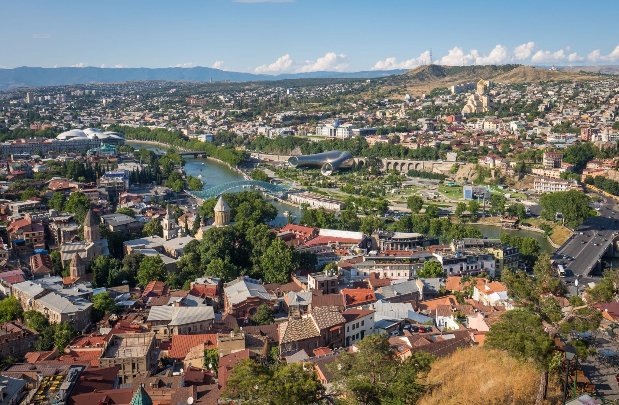 A gorgeous view of Tbilisi underneath a blue sky, buildings with orange roofs, the green river snaking through the city, a few of the modern glassy buildings poking up in the photo.