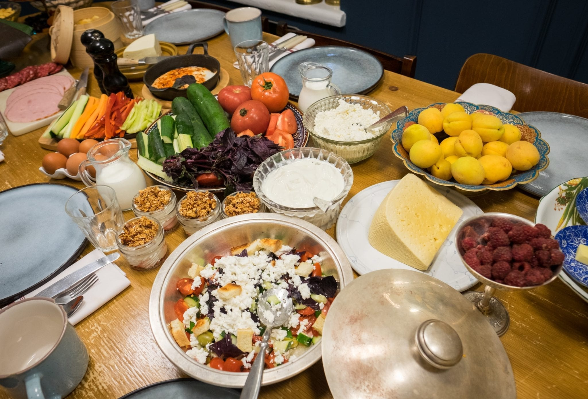 Plates of Georgian food -- salads topped with cheese, fresh vegetables, apricots, raspberries, yogurt.