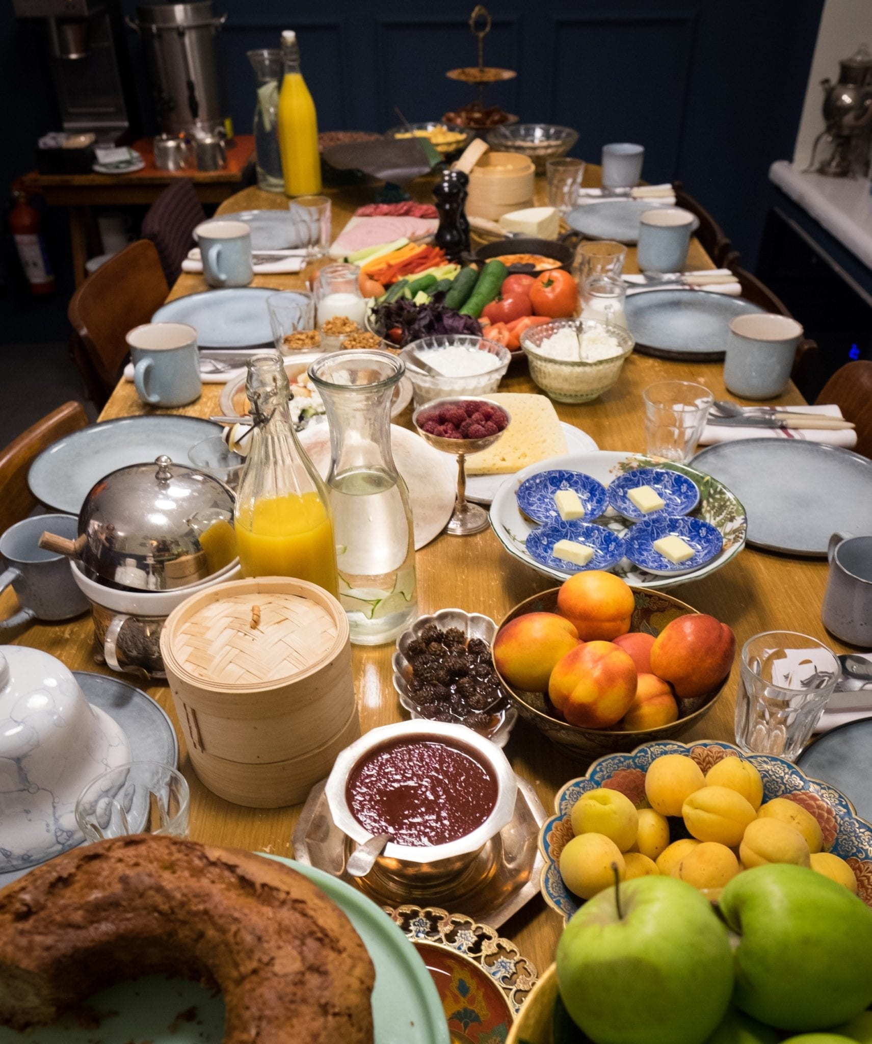 A long table brimming with breakfast: breads, fruits, pastries, cheeses, jams, all served in gorgeous blue and white dishes.