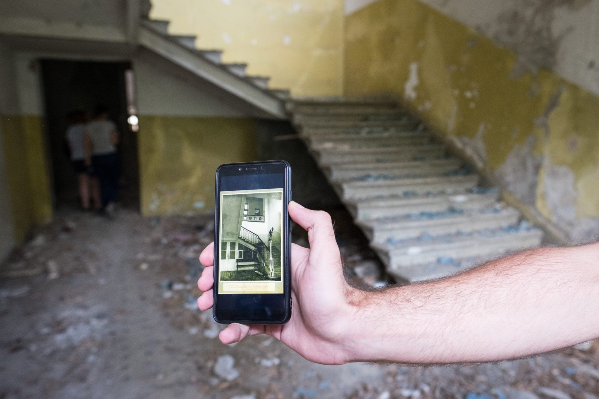 An old, broken down staircase; in the foreground is a hand holding an iPhone that shows the same staircase when it was immaculate.