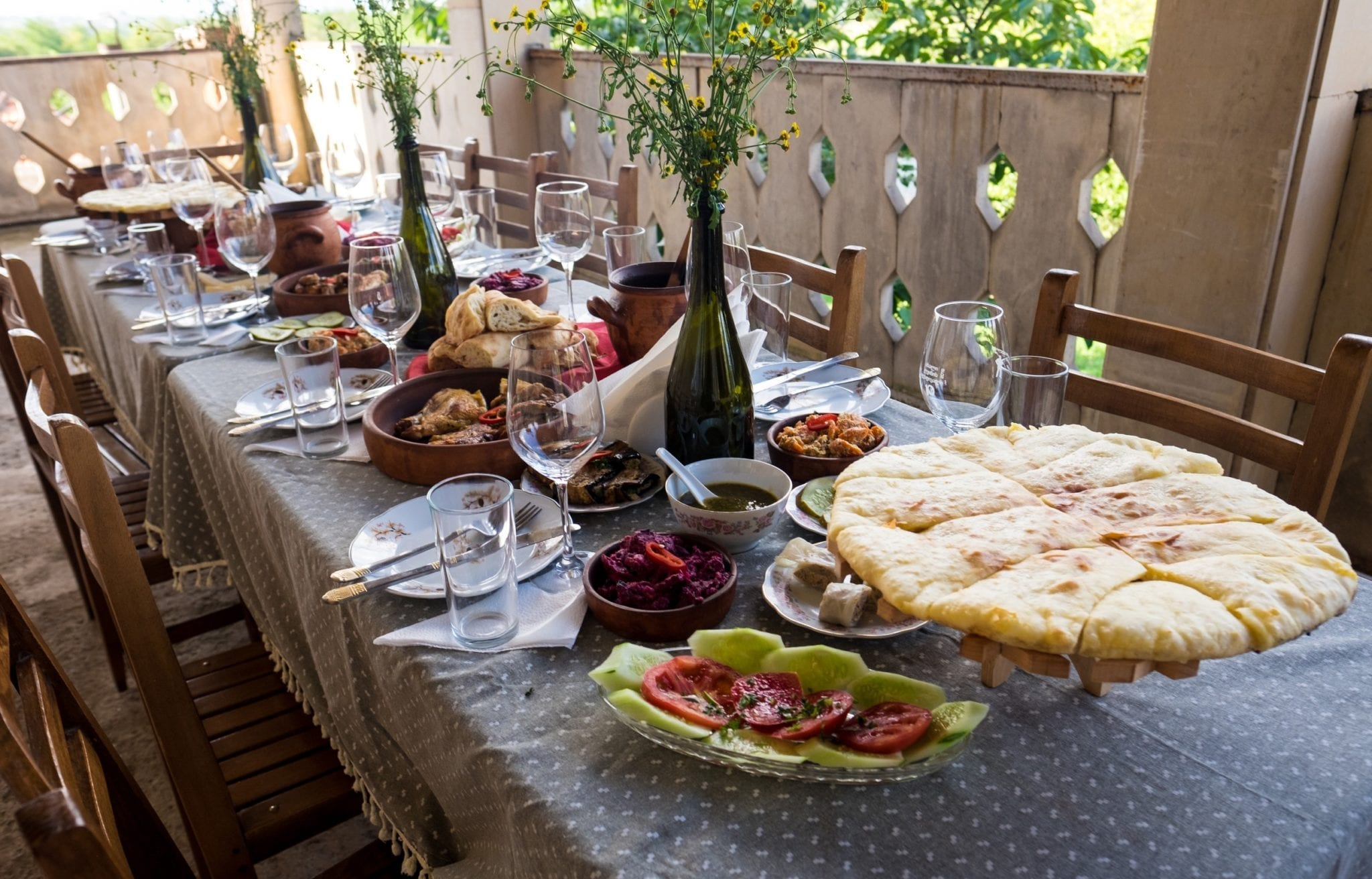 A table covered with plates of Georgian food: khachapuri (cheese pie), tomato walnut cucumber salad, roasted chicken, and lots of wine.
