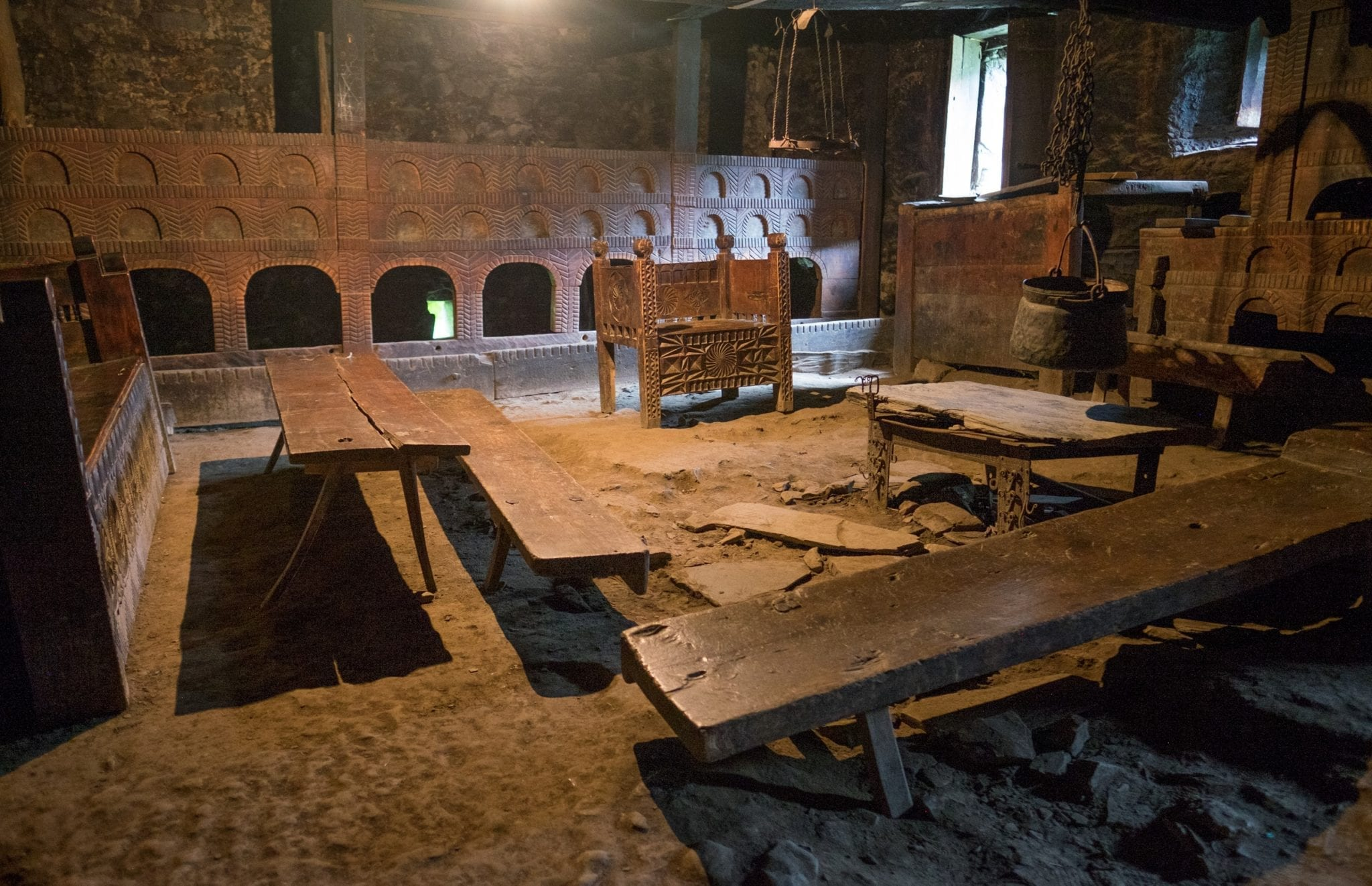 The Svan Museum, looking like an authentic Svan home from medieval times with a carved wooden chair and plain tables, in Mestia, Svaneti.