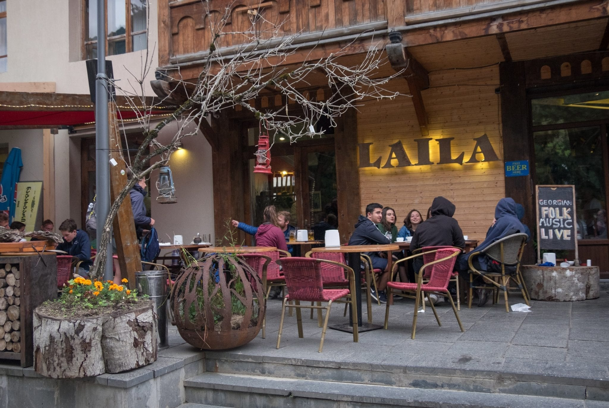 Travelers sitting outside the Laila Cad and restaurant, bundled up in the chill, in Mestia, Svaneti.