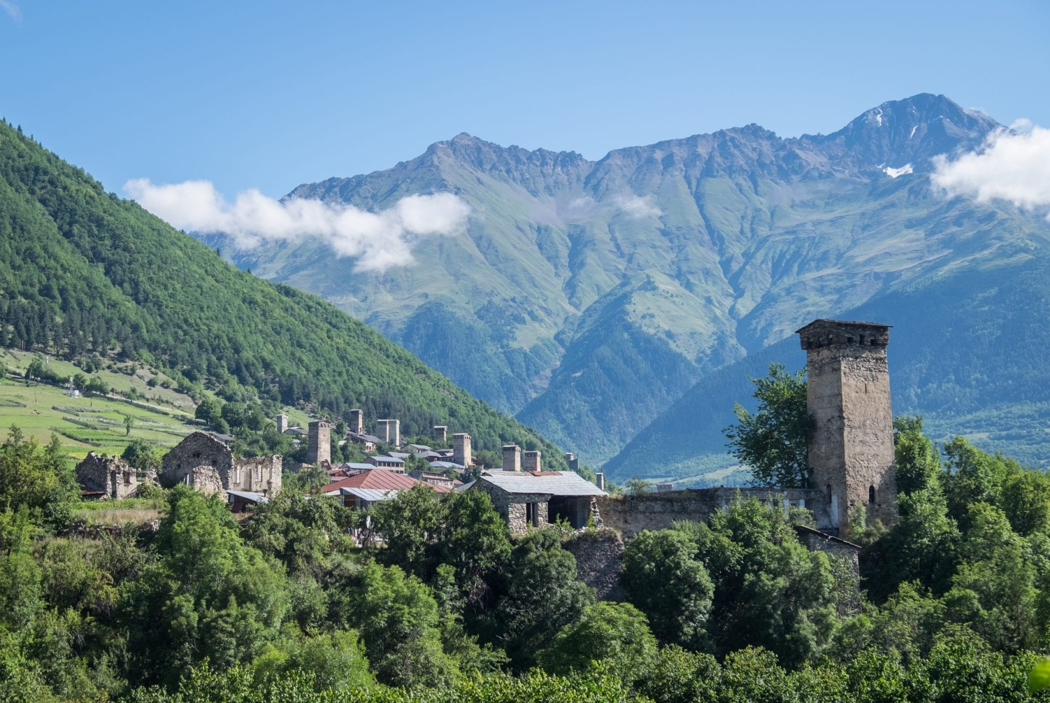 A view over Mestia: mountains in the background, clouds in the sky (lower than the mountains!) and a stone tower on the right and a village with more towers on the left.