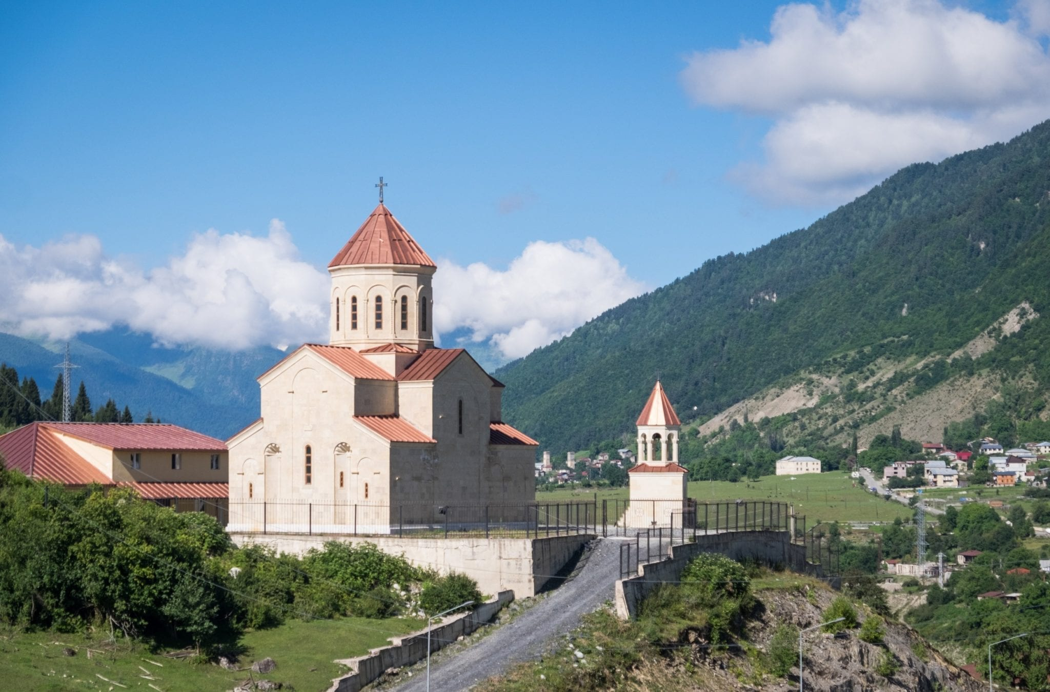 An orange-roofed church looking over the mountain landscape in Mestia, Svaneti.
