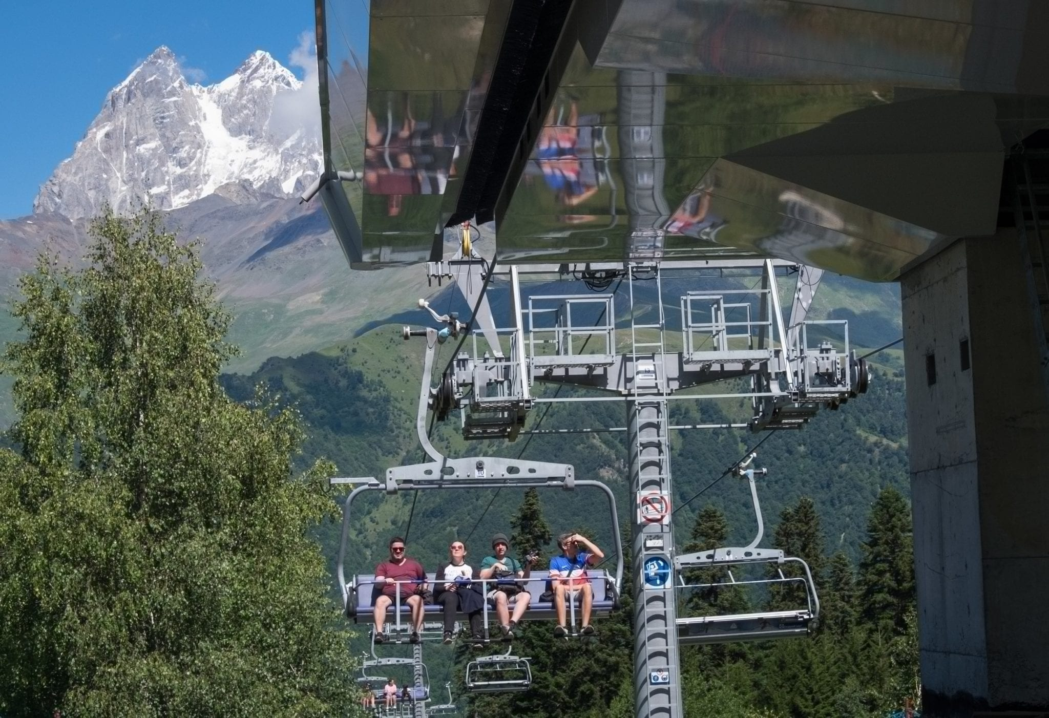 People ride a cable car as a mountain rises up behind them in front of a blue sky.