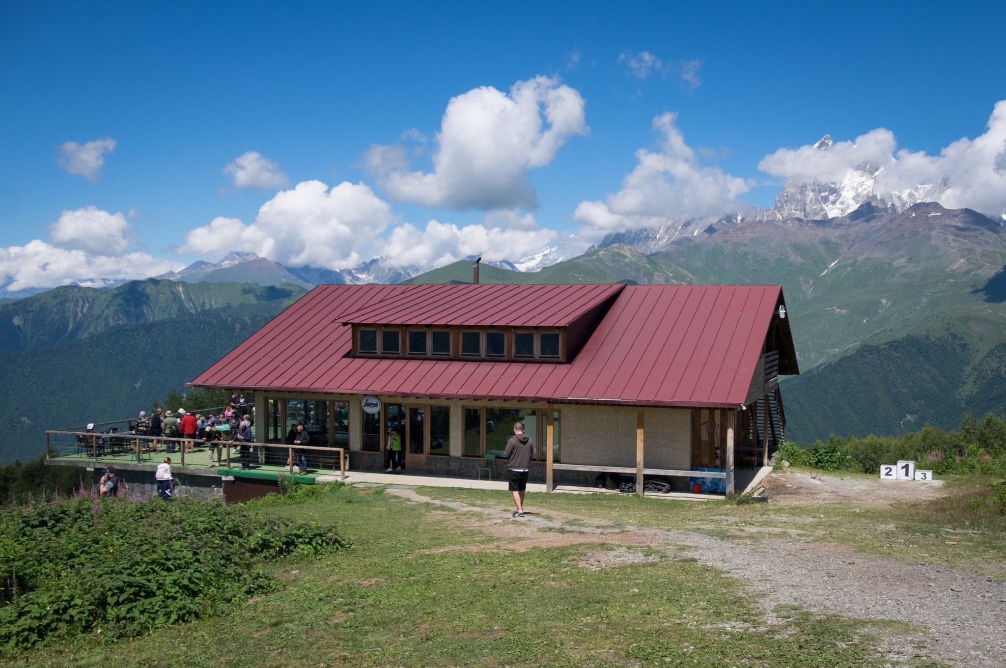 A restaurant with a maroon roof overlooks a Mountain View in Svaneti.