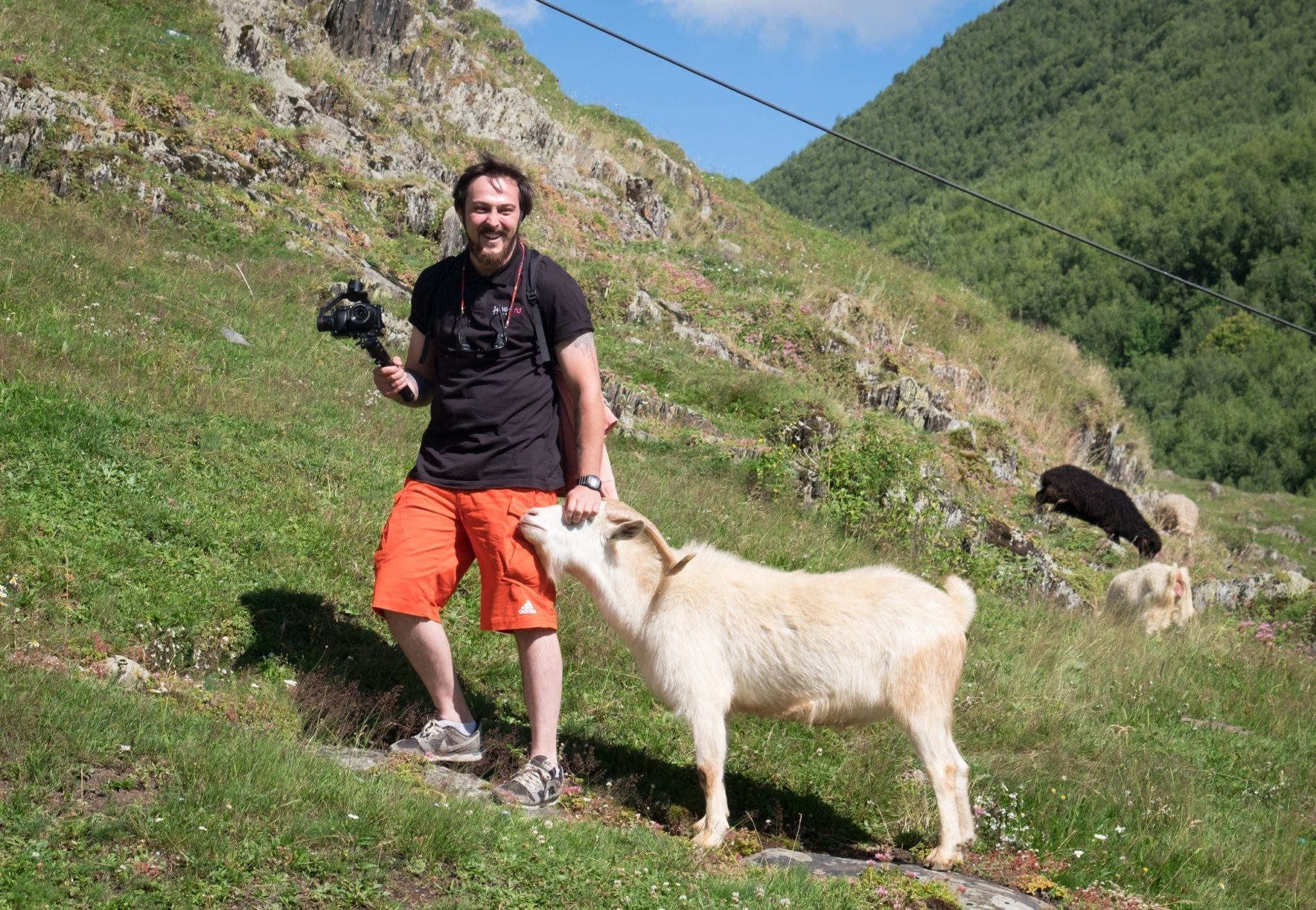 Jayway guide Gio stands on a hillside with a camera and gimbal in one hand and a goat nuzzling his hip. He strokes the goat's head and laughs.