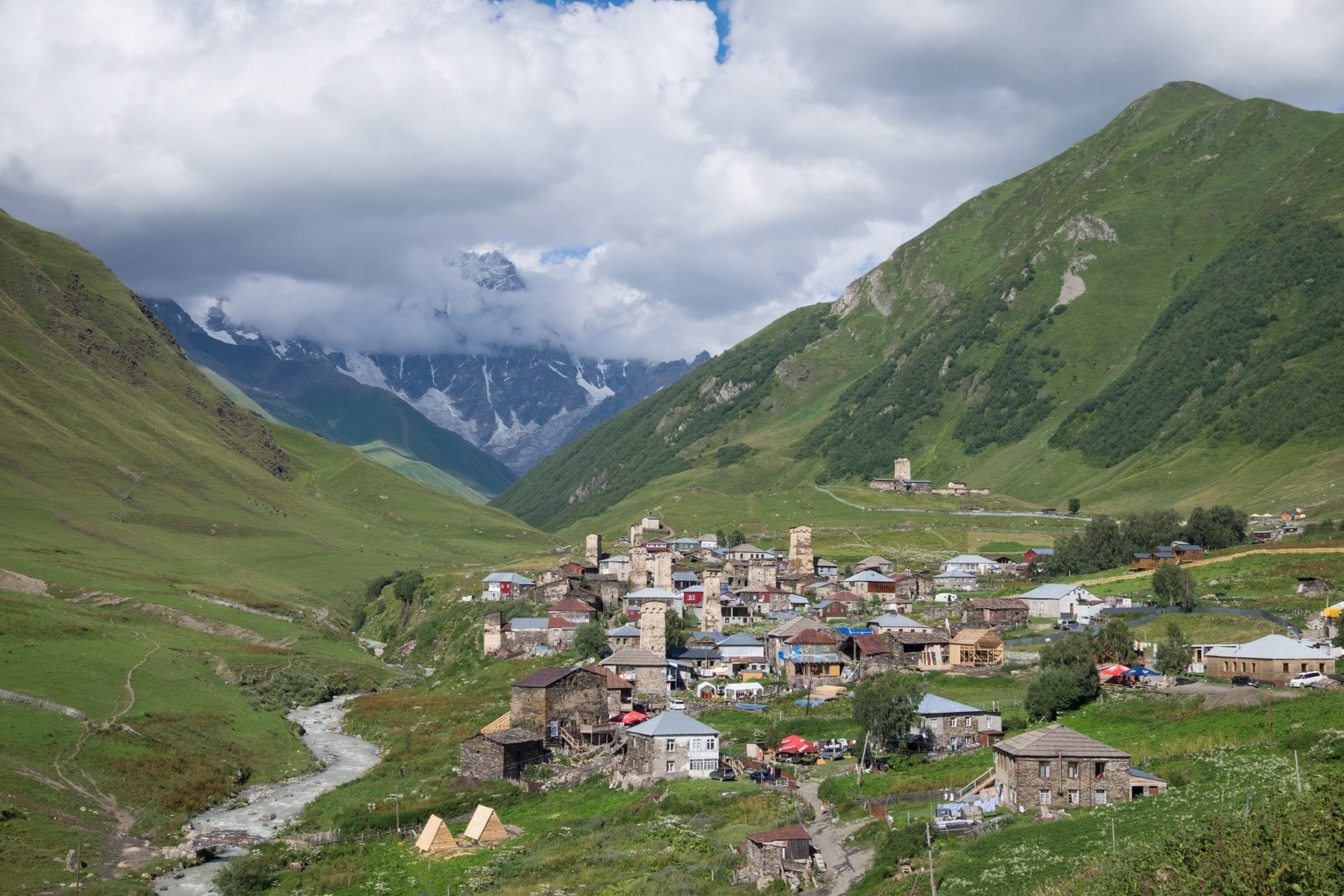 A distance view of Ushguli, with the stone towers of the village towering over the green landscape but not the surrounding green mountains.