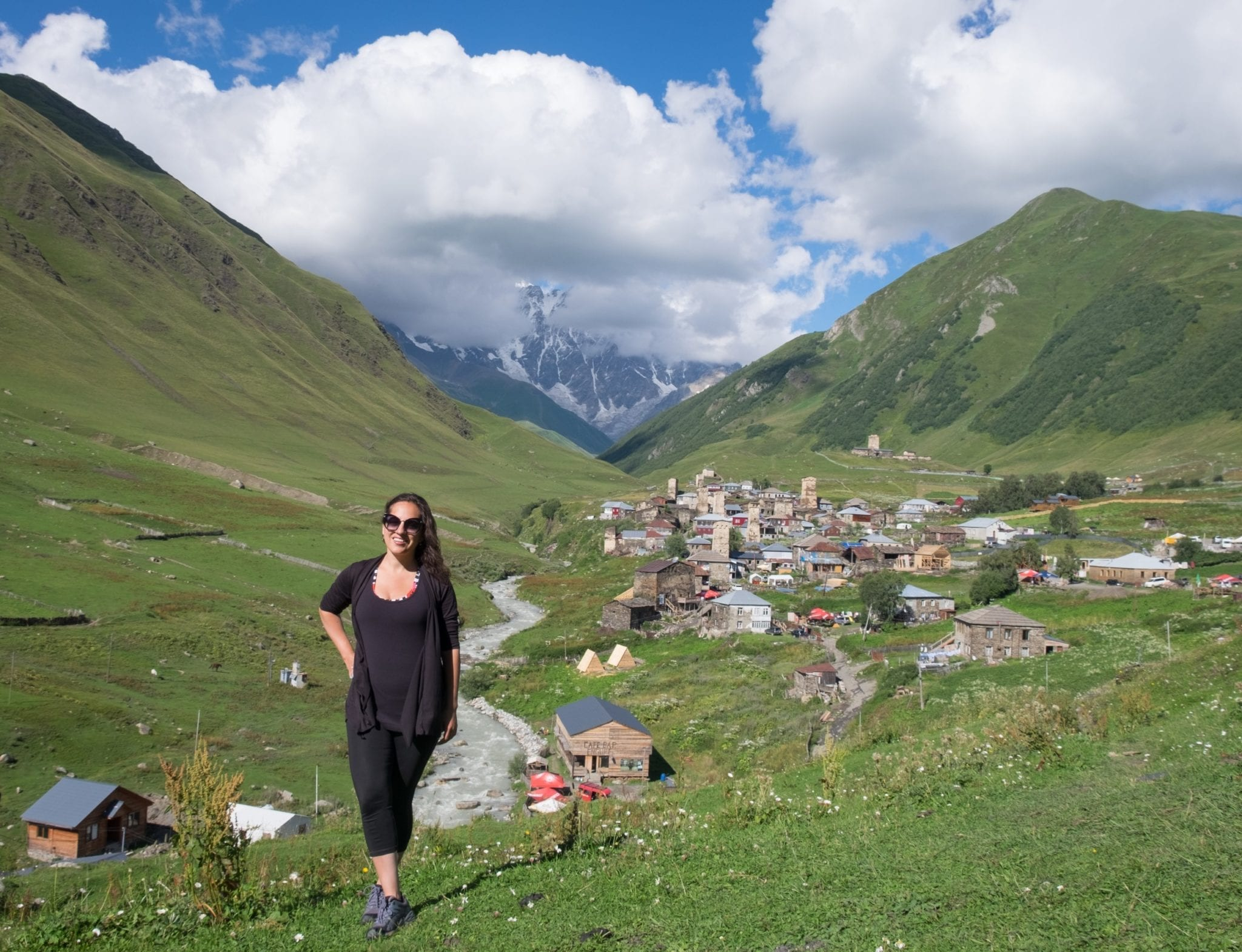 Kate stands on a grassy hill in front of the village of Ushguli in Georgia, with its stone towers. Behind the village is a mountain partially obscured by clouds.