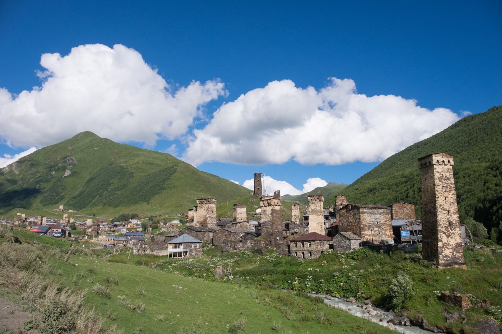 On the right, the village of Chazhashi in Ushguli, stone towers pointing into the air. In the background are green grassy mountains underneath a blue sky with clouds,