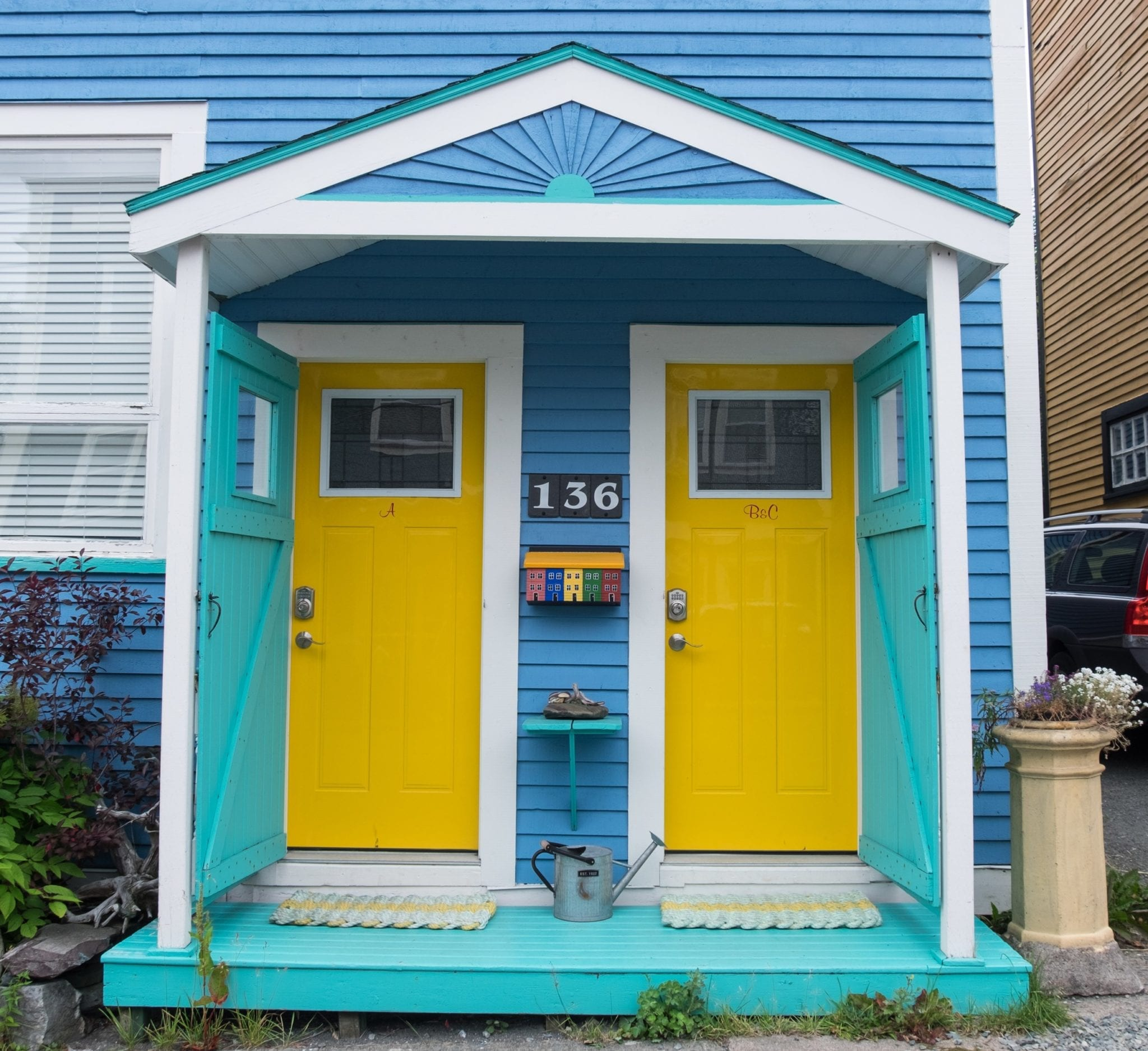 A blue house with two bright yellow doors side by side, surrounded by turquoise trim, in St. John's.