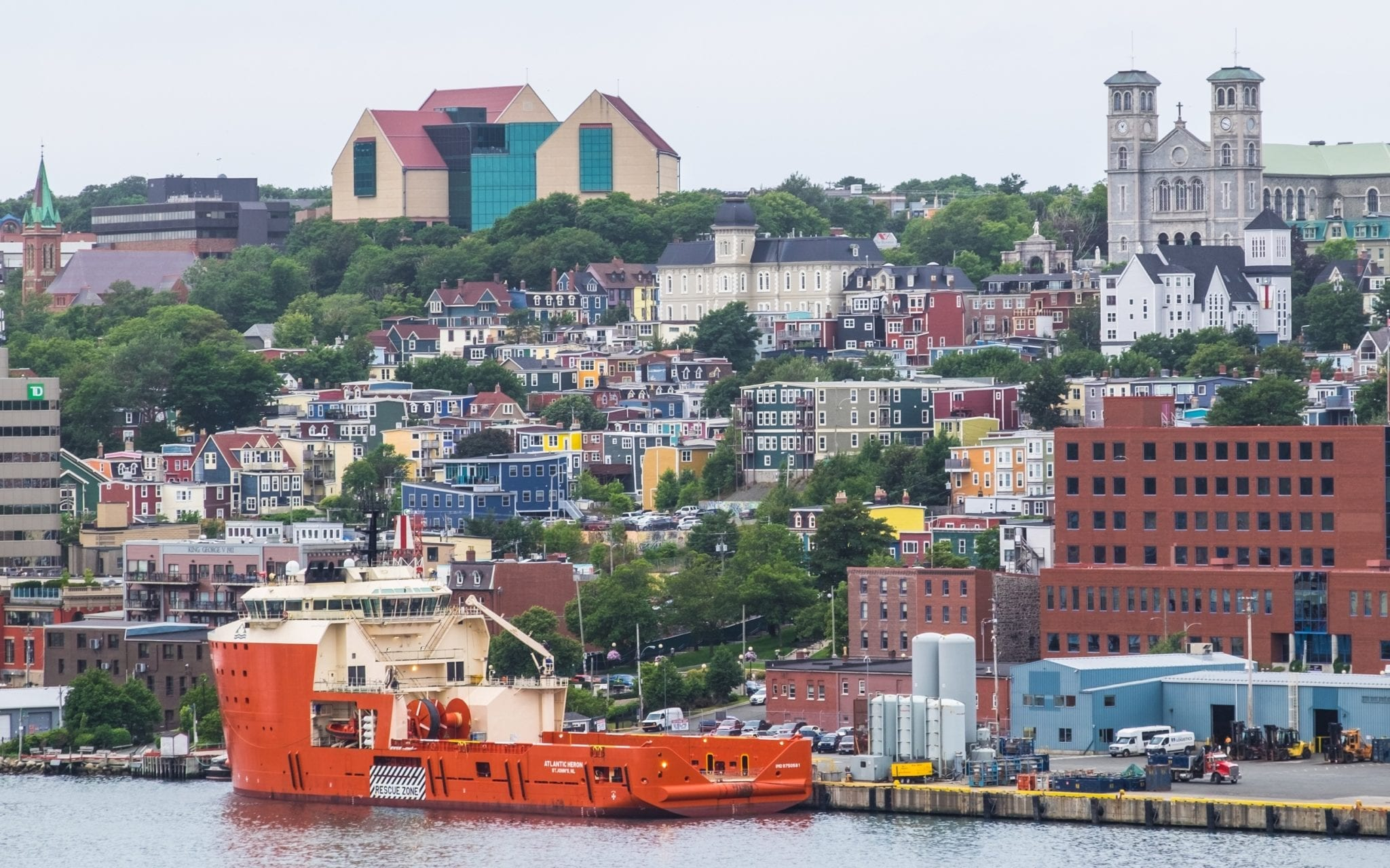 A shot of St. John's from a distance. You can see all the colorful homes on Jelly Bean Row, and a bright yellow ship in front.