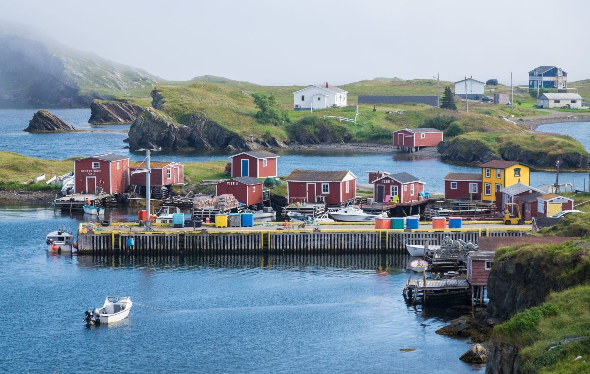 Red fishing cottages on a still bay with islands and cloud-wrapped cliffs in the background in Newfoundland.